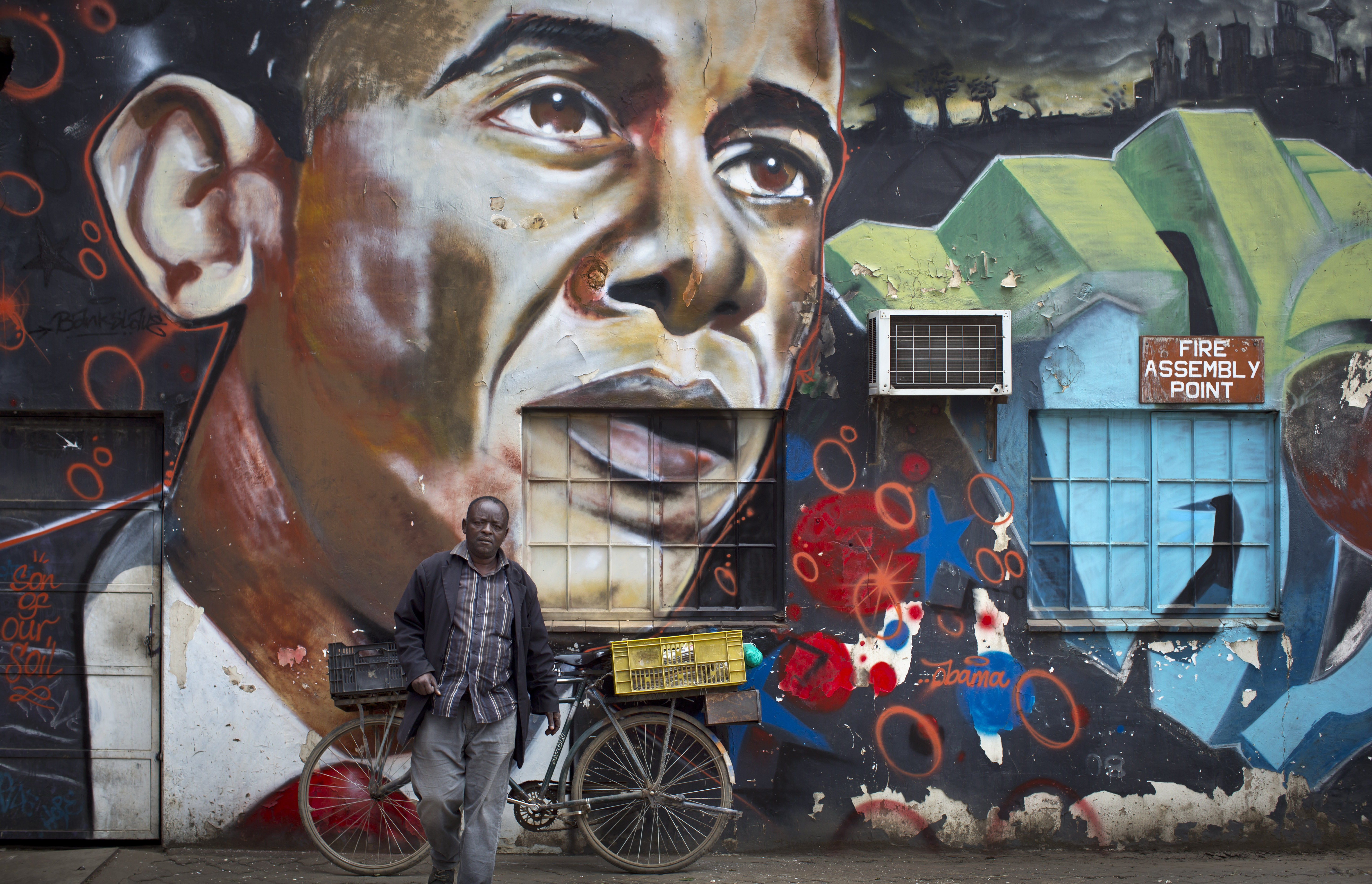 A man walks away after leaning his bicycle against a mural of President Barack Obama, created by the Kenyan graffiti artist Bankslave, at the GoDown Arts Centre in Nairobi on July 22, 2015.
