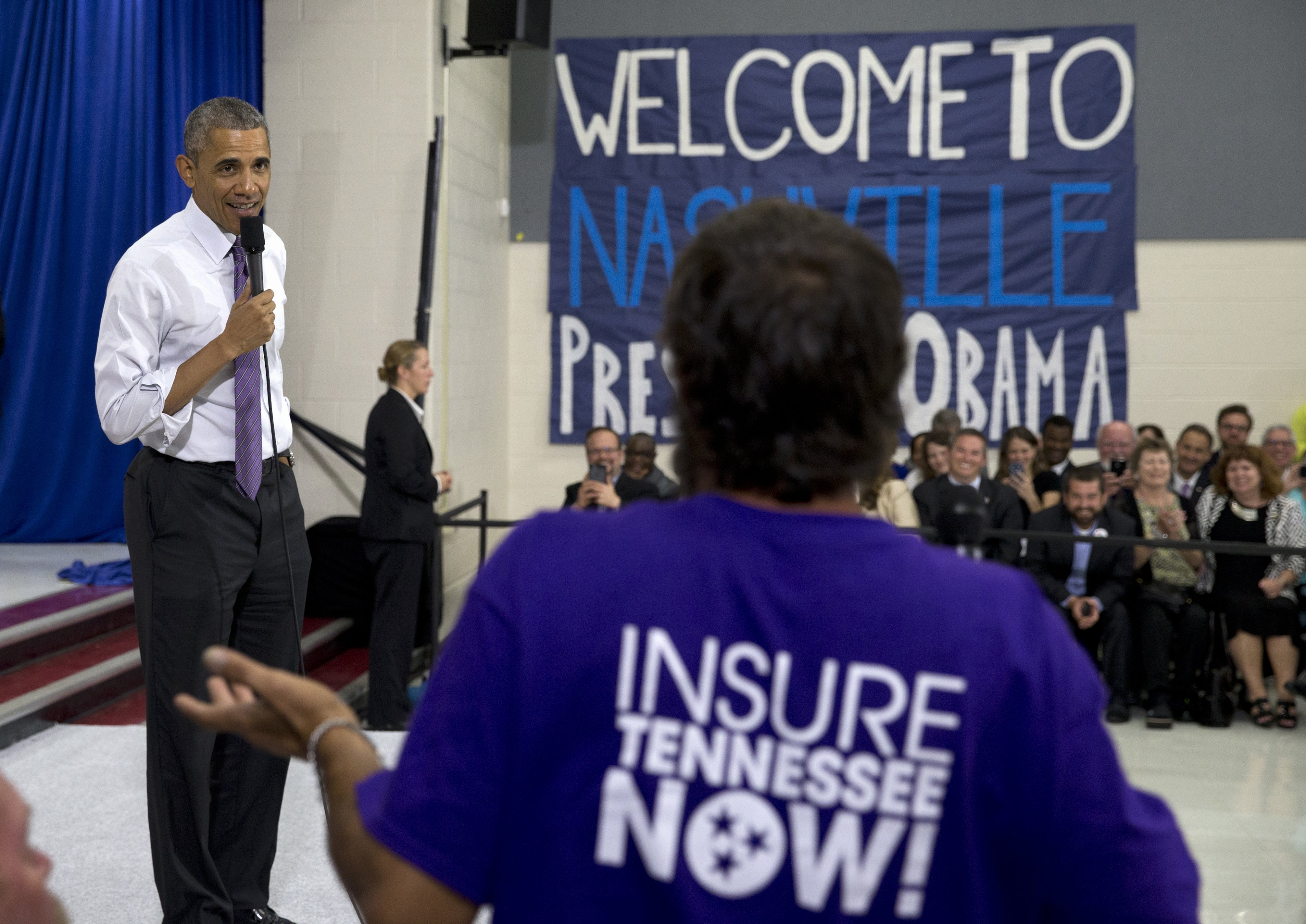 President Barack Obama talks to a man in the audience as he takes questions at Taylor Stratton Elementary School in Nashville on July 1, 2015, about the Affordable Care Act.