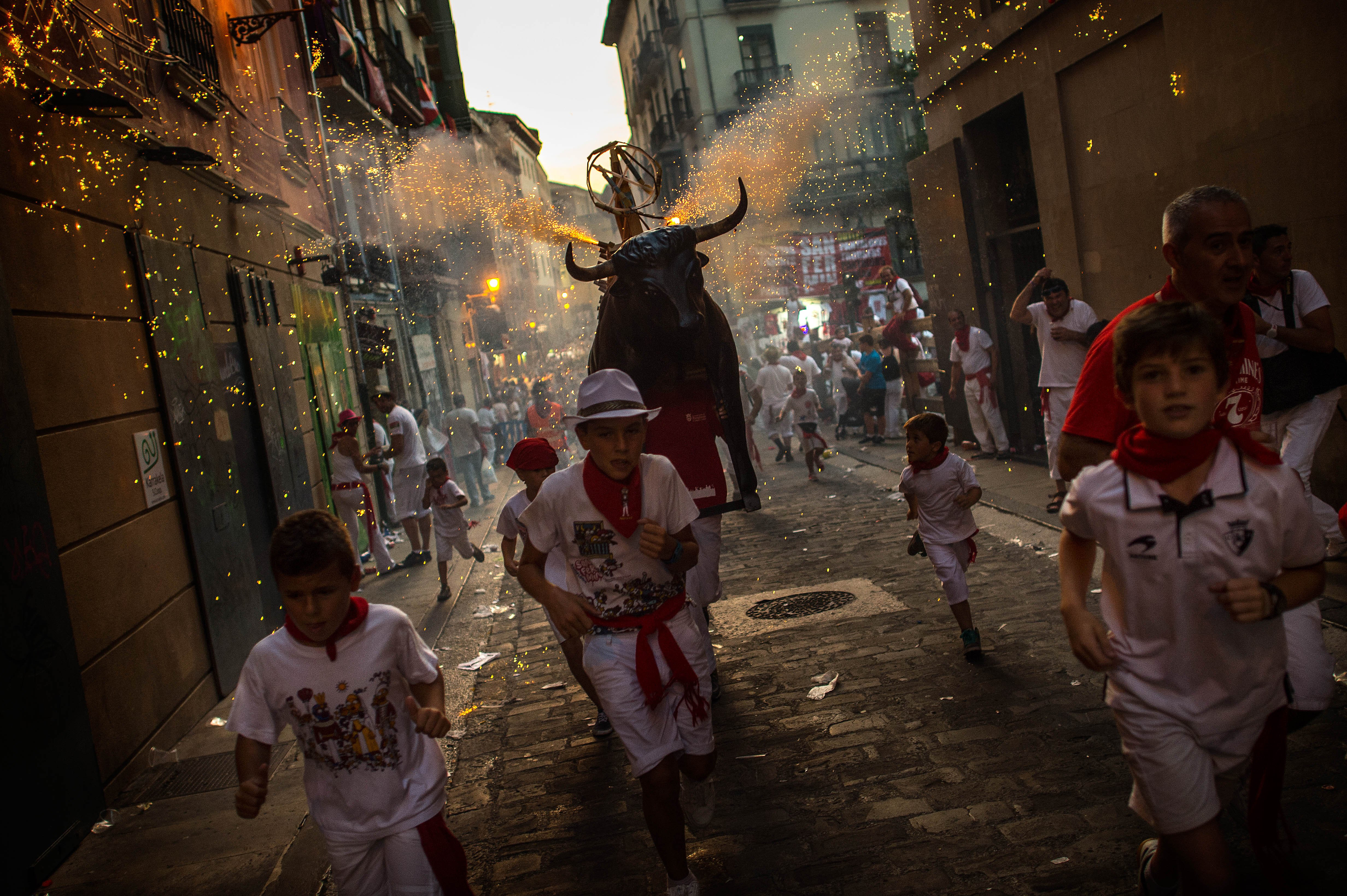 Revellers and children are 'chased' by the 'Toro de Fuego' (Flaming bull) as it runs the streets during the opening day of the San Fermin Running of the Bulls fiesta on July 6, 2015 in Pamplona, Spain.