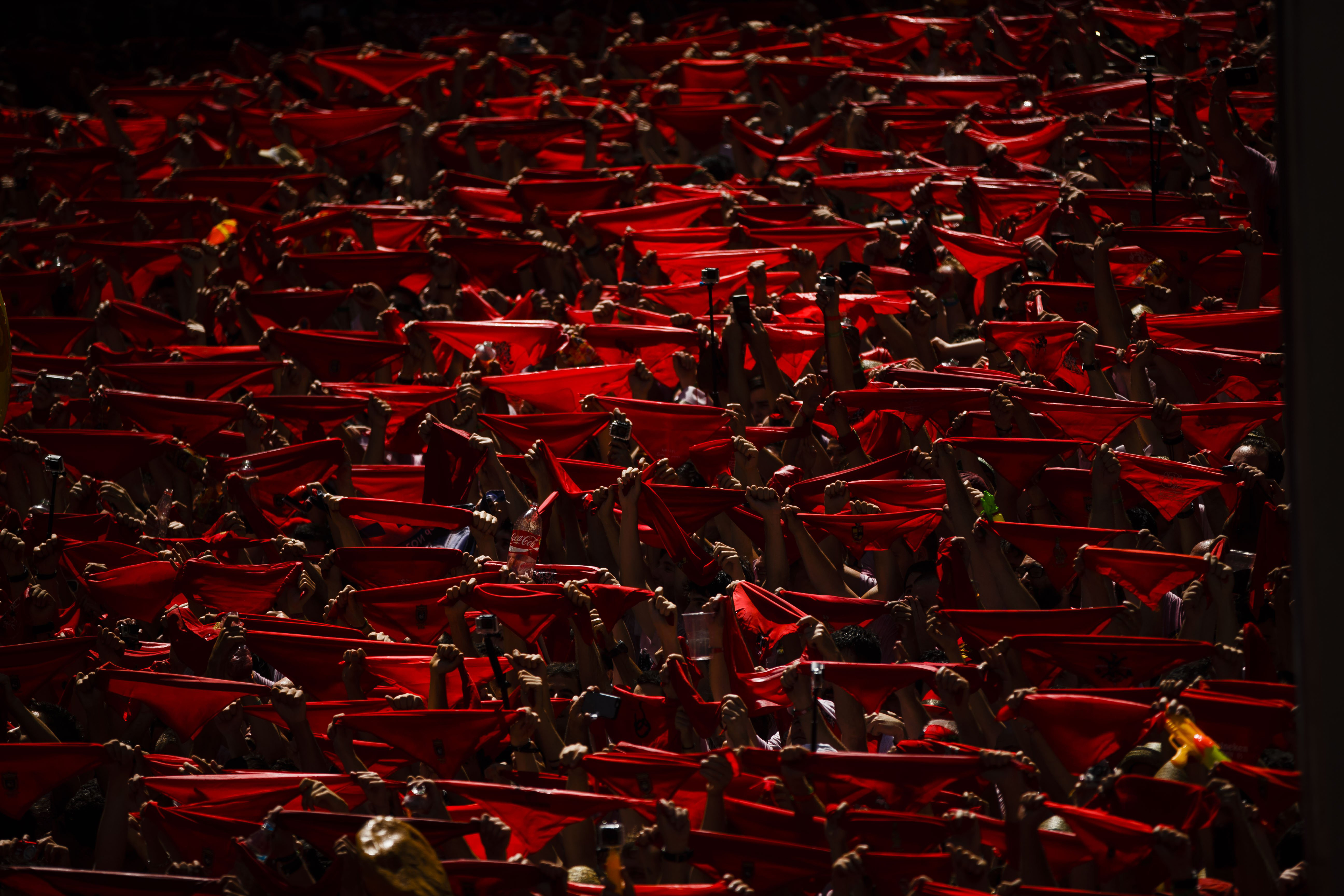 Revelers hold up traditional red neckties at the official opening of the 2015 San Fermin festival in Pamplona, Spain on July 6, 2015.