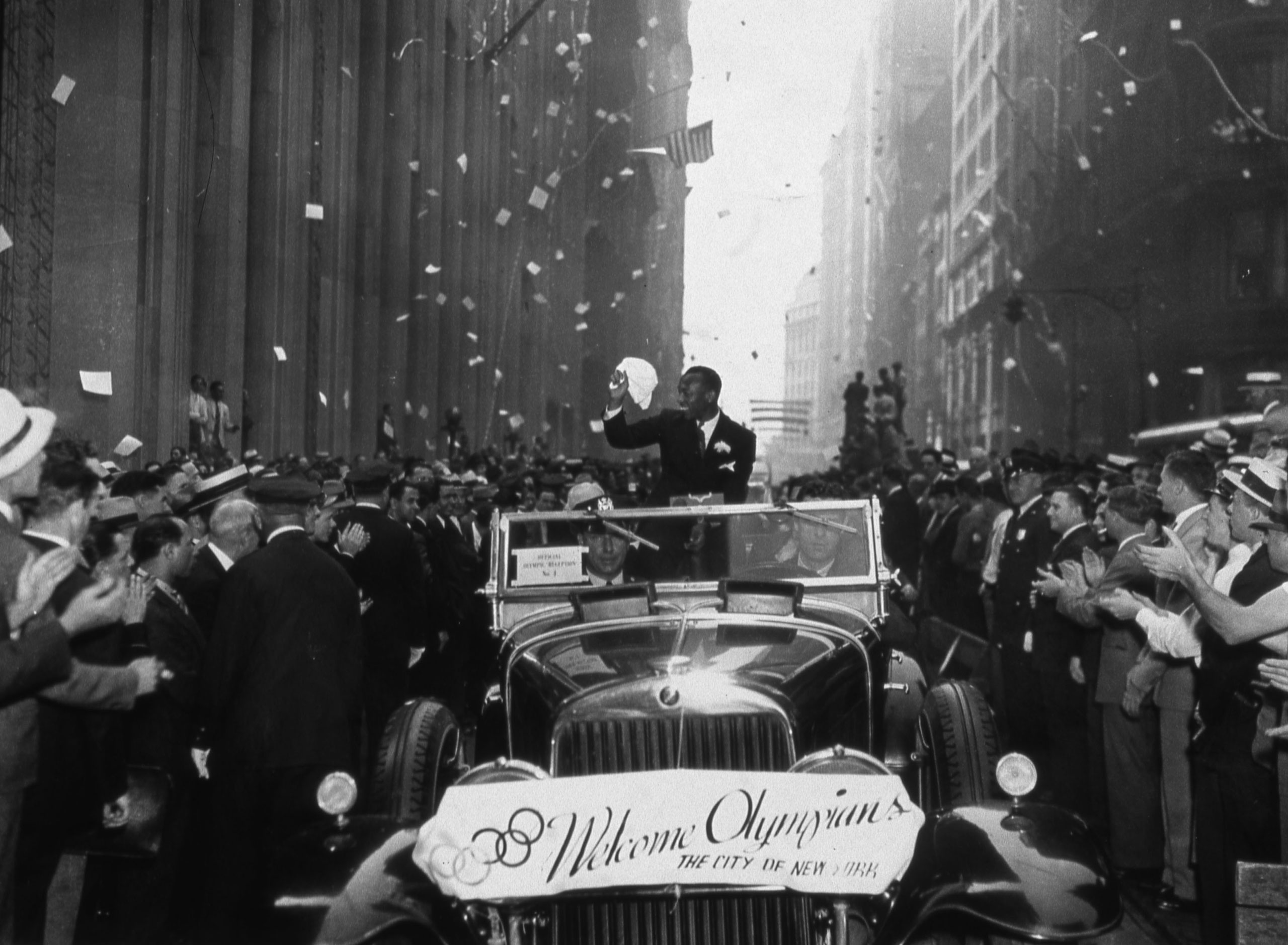 American athlete and Olympic gold medal winner Jesse Owens waves at fans  during a ticker tape parade in honor of the U.S. athletes who competed in the Berlin Olympic Games, in New York, on Sept. 3, 1936.