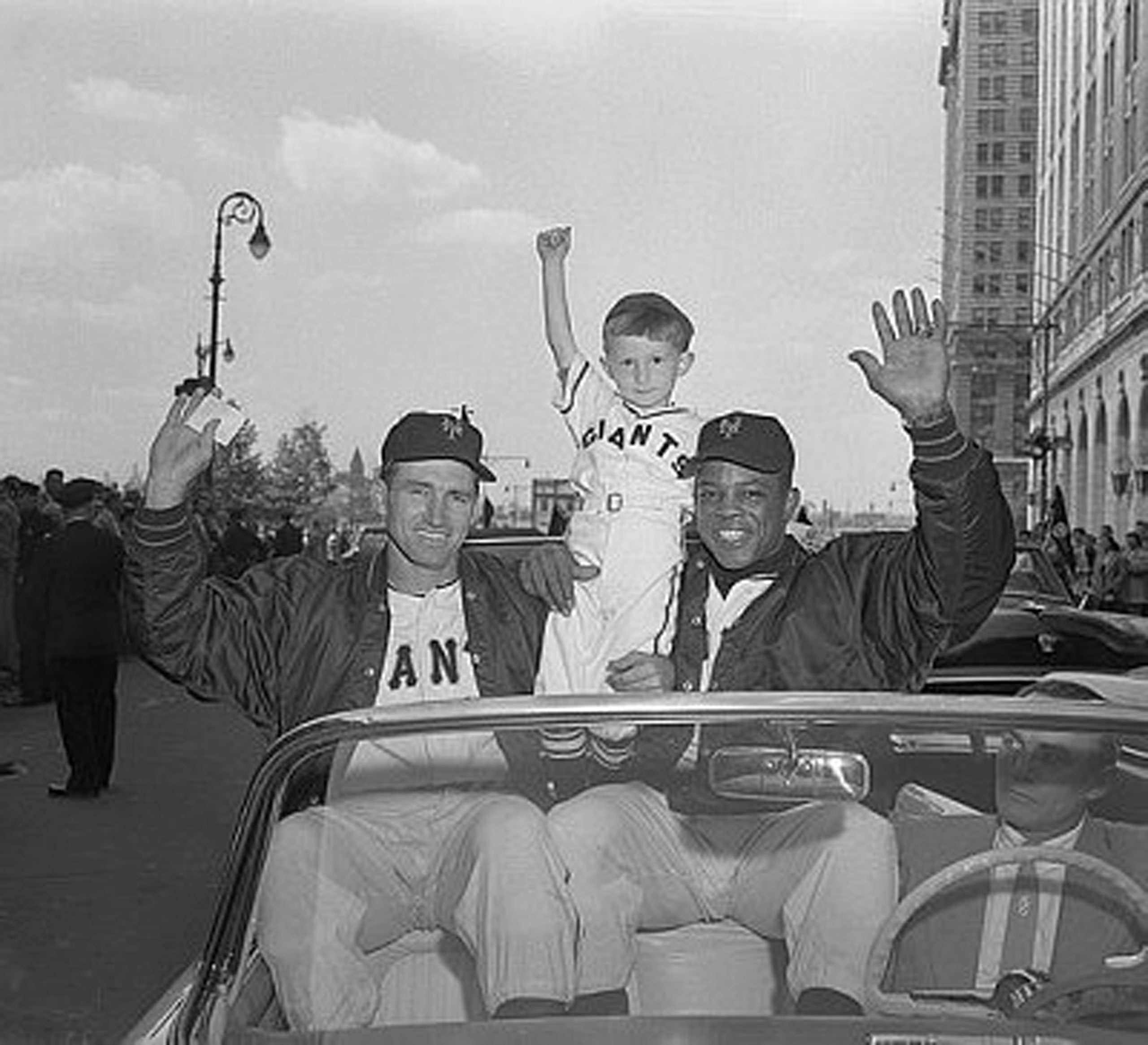 Alvin Dark and Willie Mays of the National League champion New York Giants, with a young fan (Kevin Currey, 4) during a parade on Sept. 27, 1954,