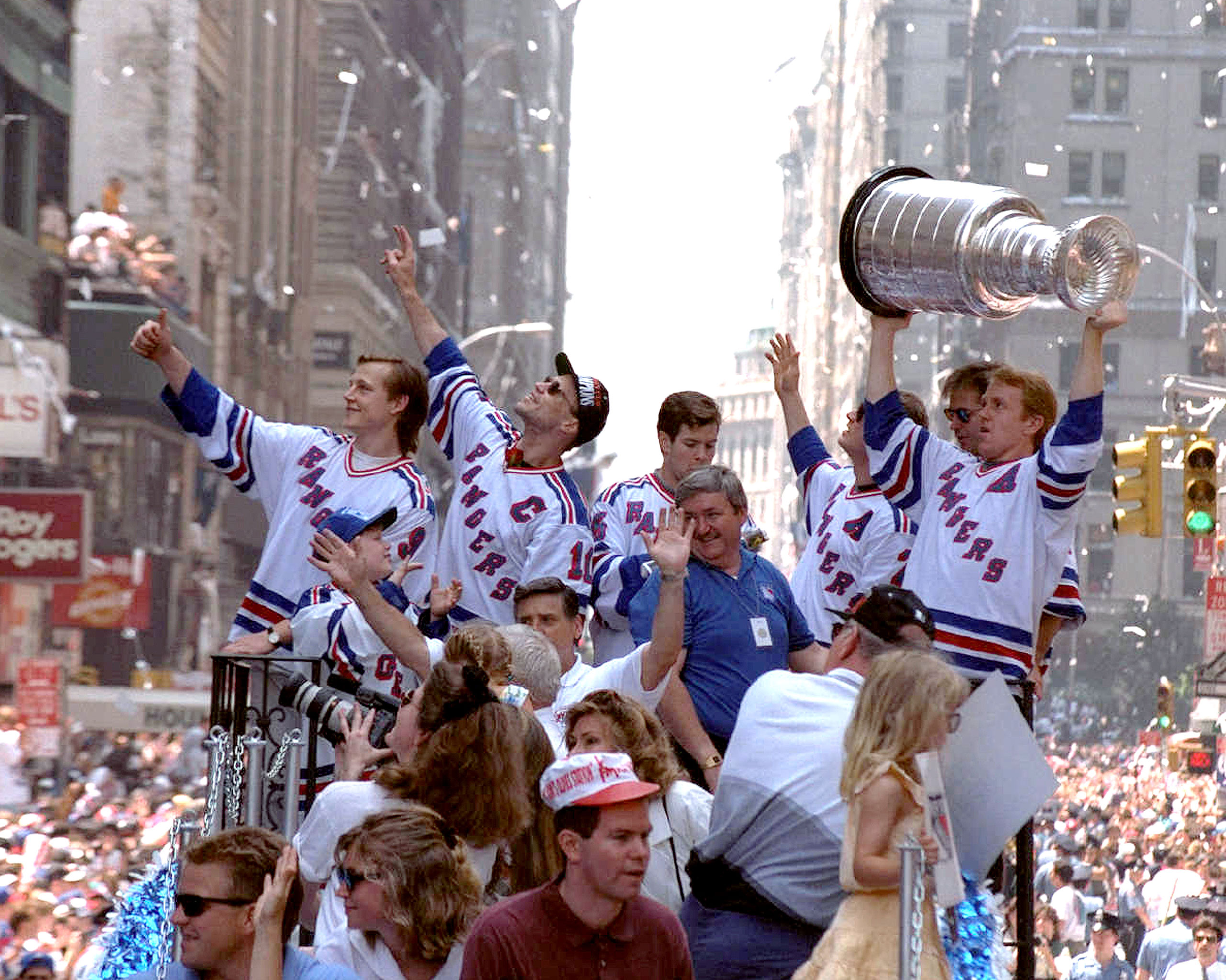 Adam Graves (far left) and Captain Mark Messier (sunglasses) with Ranger teammates during a ticker-tape  parade in honor of their Stanley Cup win, on June 17, 1994. Brian Leetch holds the cup,