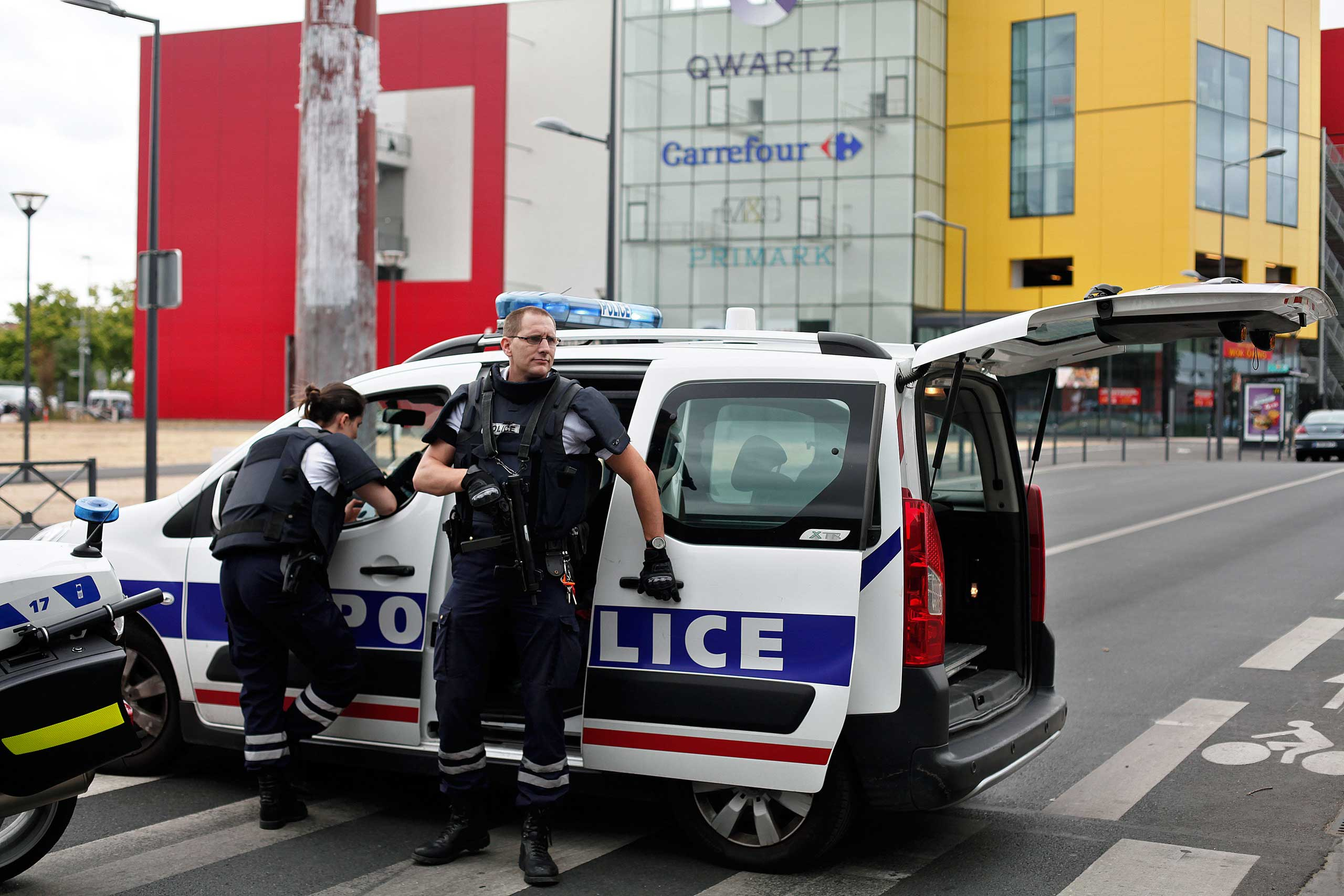Police officers stand outside a suburban clothing store, in Villeneuve-la-Garenne, north of Paris on July 13, 2015.
