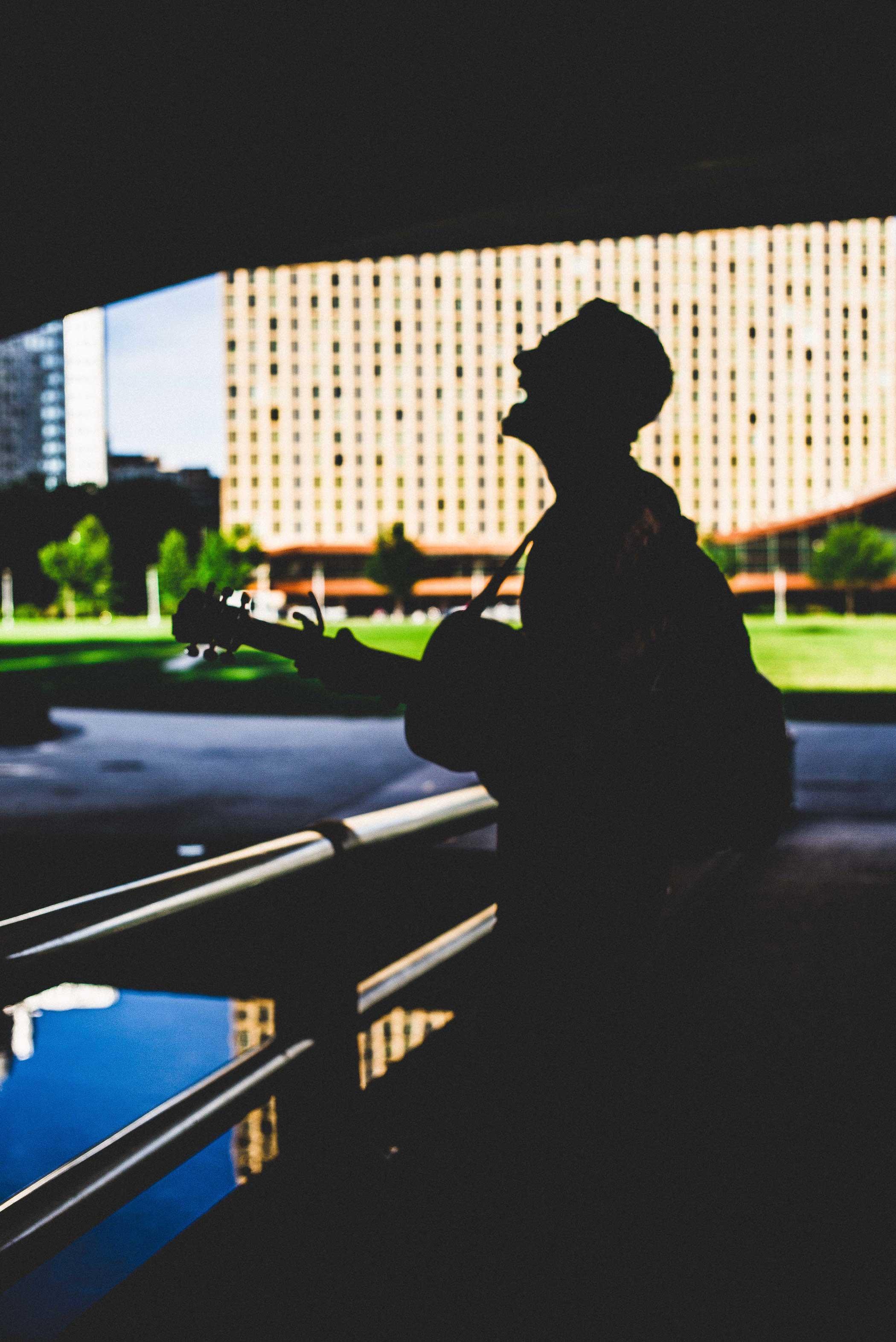 A man play guitar under a bridge on June 24, 2015.