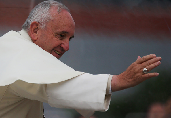 Pope Francis waves to the crowd from the Popemobile while making his way to celebrate an open-air Mass on July 9, 2015 in Santa Cruz, Bolivia.
