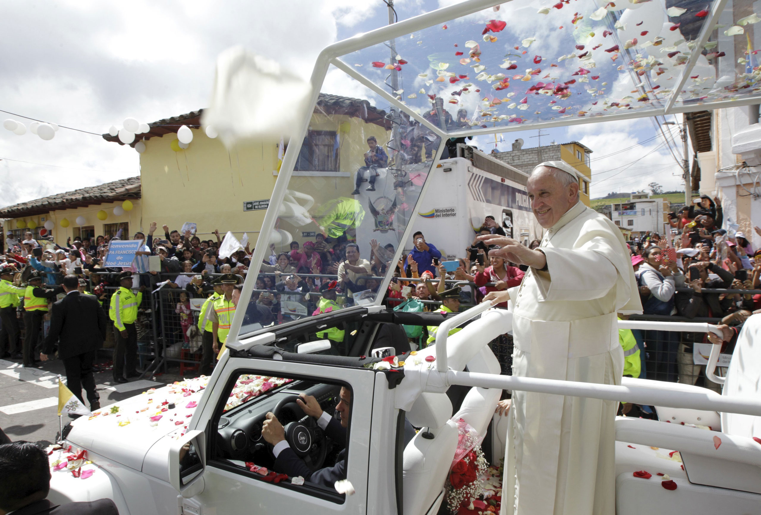 Pope Francis waves to the faithful from a popemobile in El Quinche, Ecuador, on July 8, 2015.