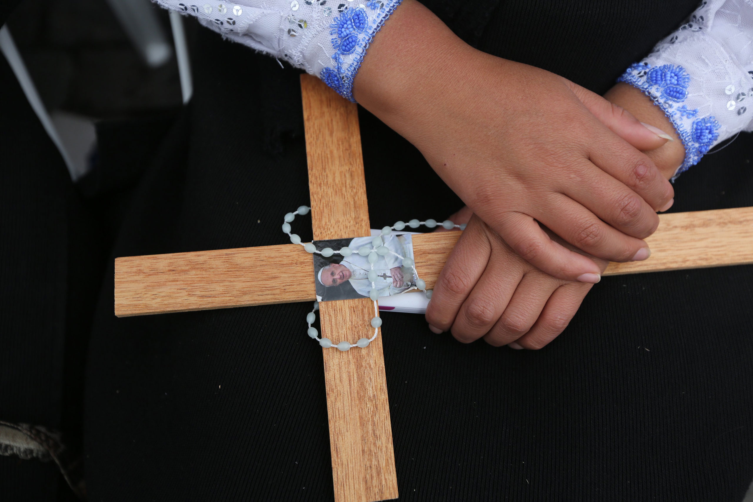 A woman holds a rosary and a wooden cross with an image of Pope Francis as she waits for the arrival of the Pontiff in San Francisco square in Quito, Ecuador, on July 7, 2015.