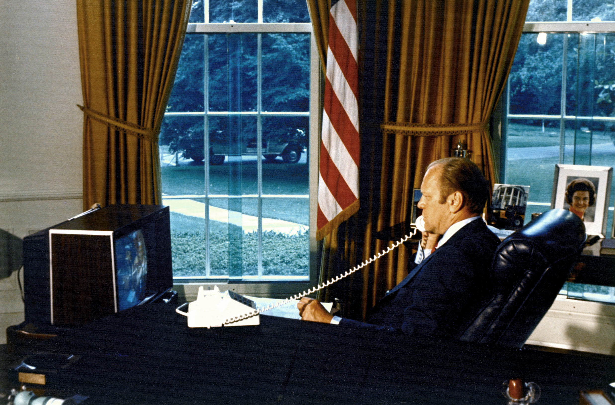 President Gerald R. Ford watches crewmen Tom Stafford, Donald Slayton and Valeriy Kubasov on a television as he talks to them by phone while they orbited the Earth on July 18, 1975. The American Apollo spacecraft and Soviet Soyuz spacecraft were docked.