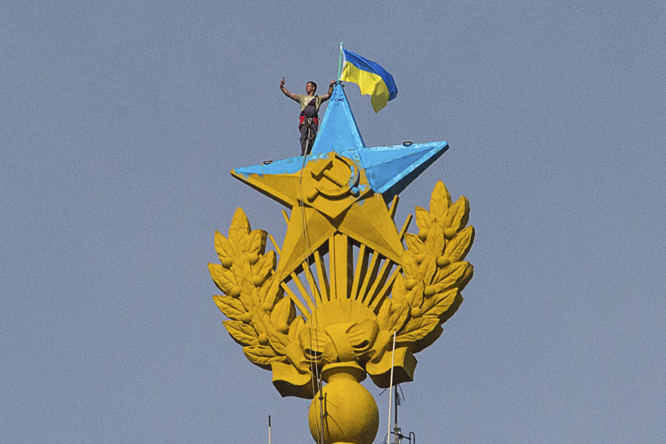 A man takes a 'selfie' as he stands with a Ukrainian flag on a Soviet-style star atop the spire of a building in Moscow.