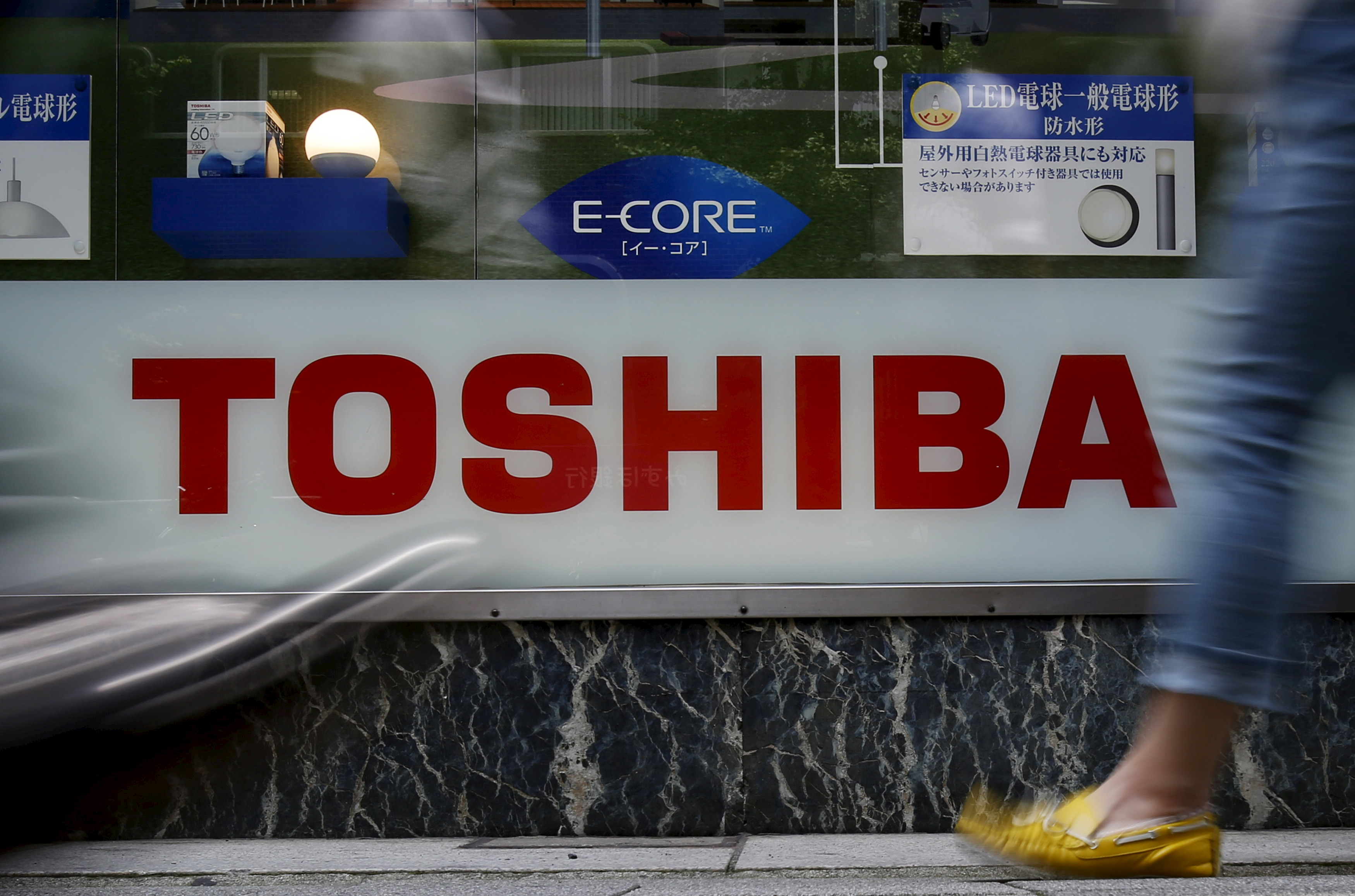 Pedestrians walk past a logo of Toshiba Corp outside an electronics retailer in Tokyo, Japan, June 25, 2015