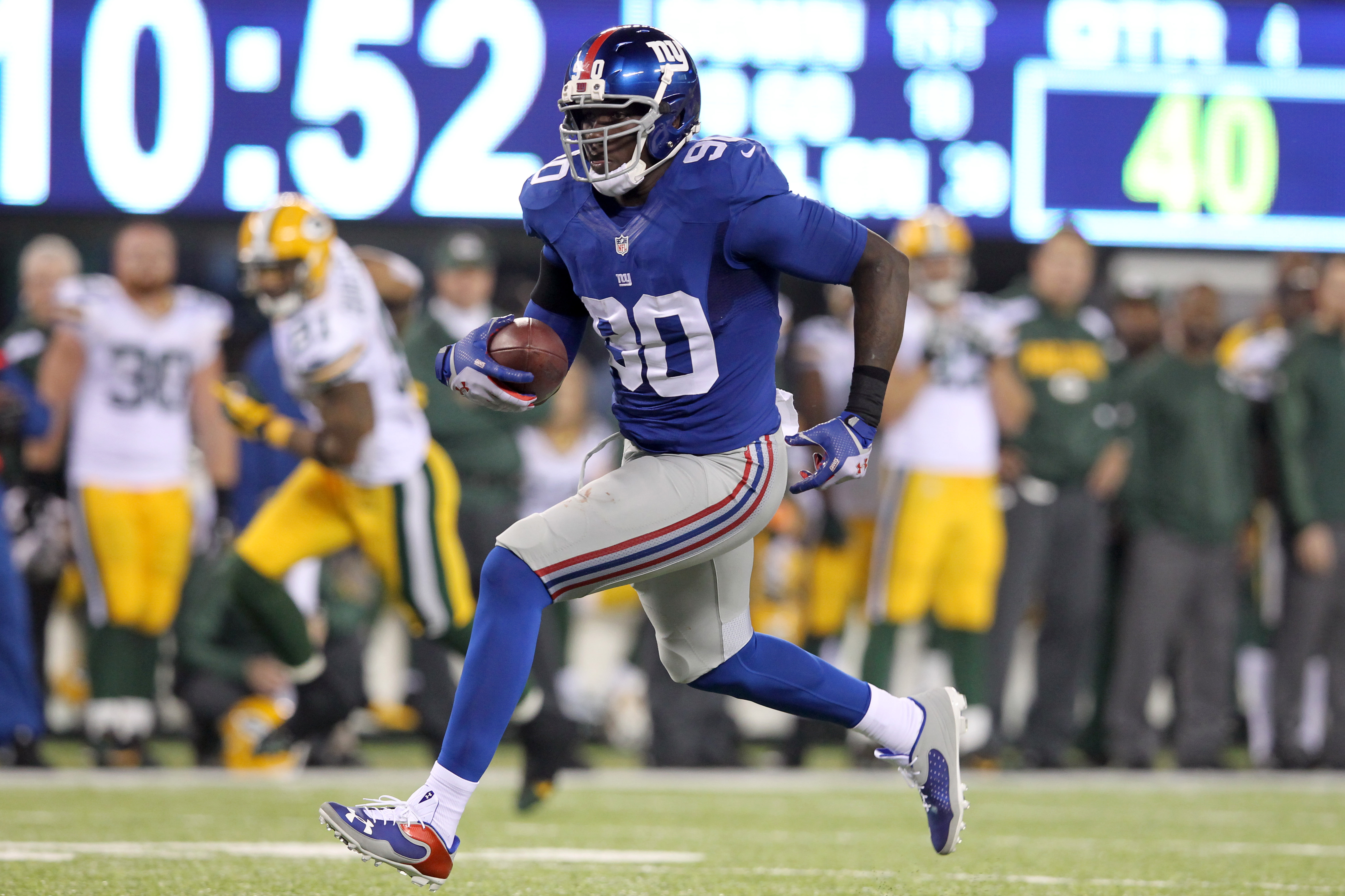 New York Giants defensive end Jason Pierre-Paul runs back an interception against the Green Bay Packers for a touchdown during the fourth quarter of a game at MetLife Stadium on November 17, 2013.