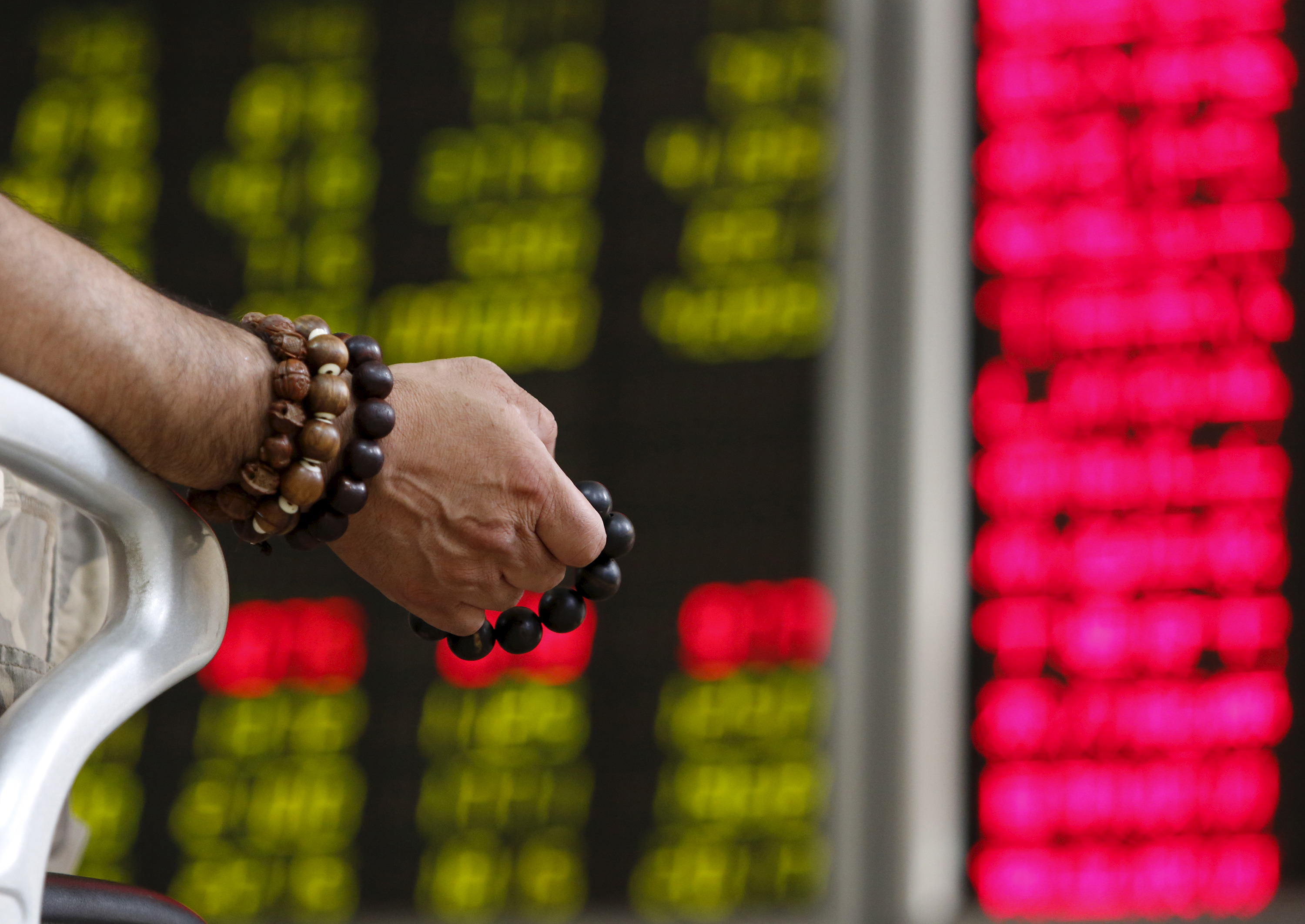 An investor holds onto prayer beads as he watches a board showing stock prices at a brokerage office in Beijing, China, July 6, 2015