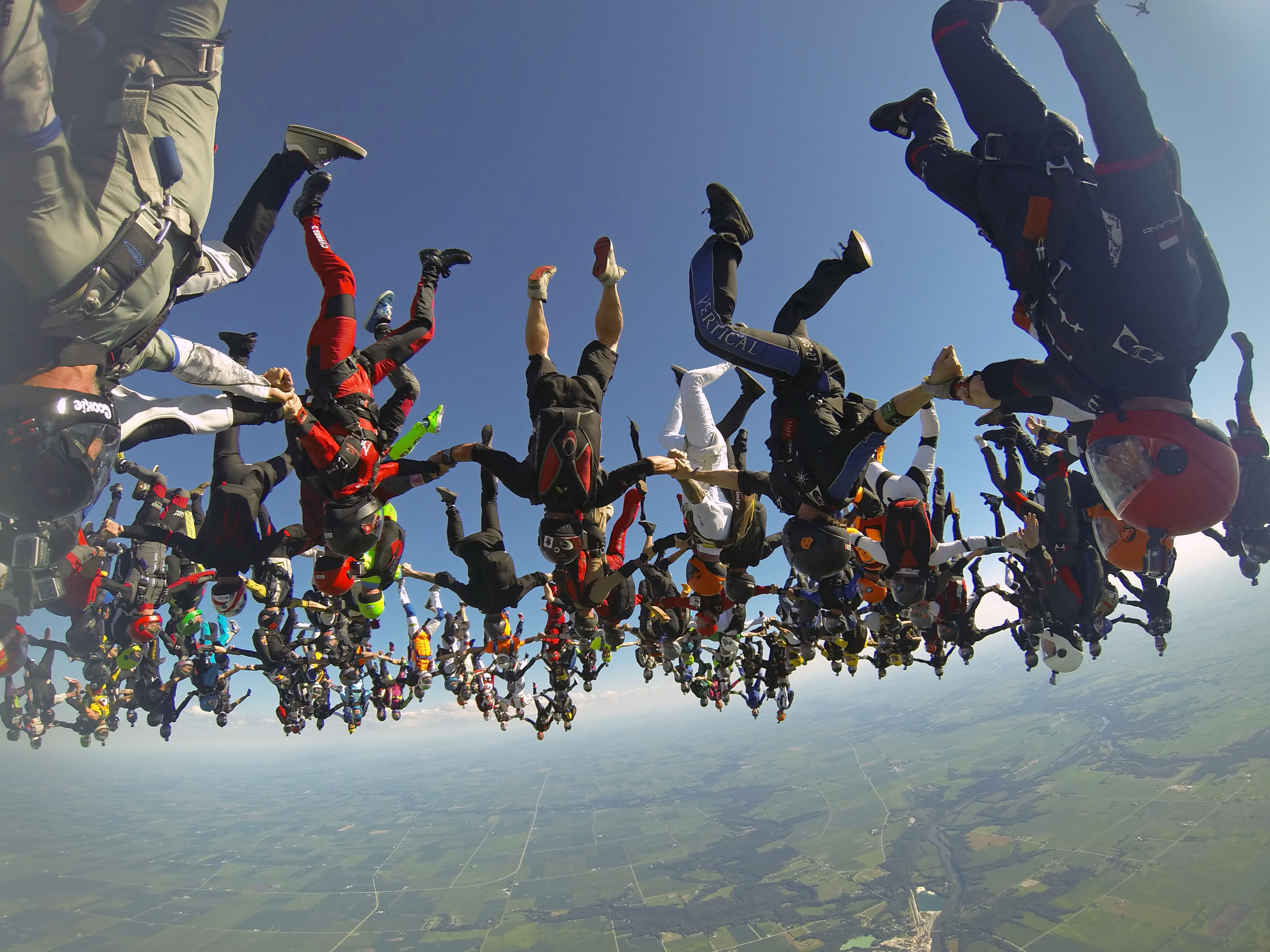 Members of an international team of skydivers join hands flying head-down to build their world record skydiving formation on July 31, 2014, over Ottawa, Ill.