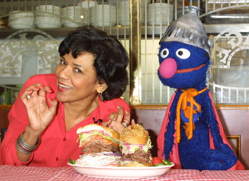 Sonia Manzano, who plays Maria Rodriquez on  Sesame Street,  and the muppet Grover at an event in New York City on Feb. 27, 2002.