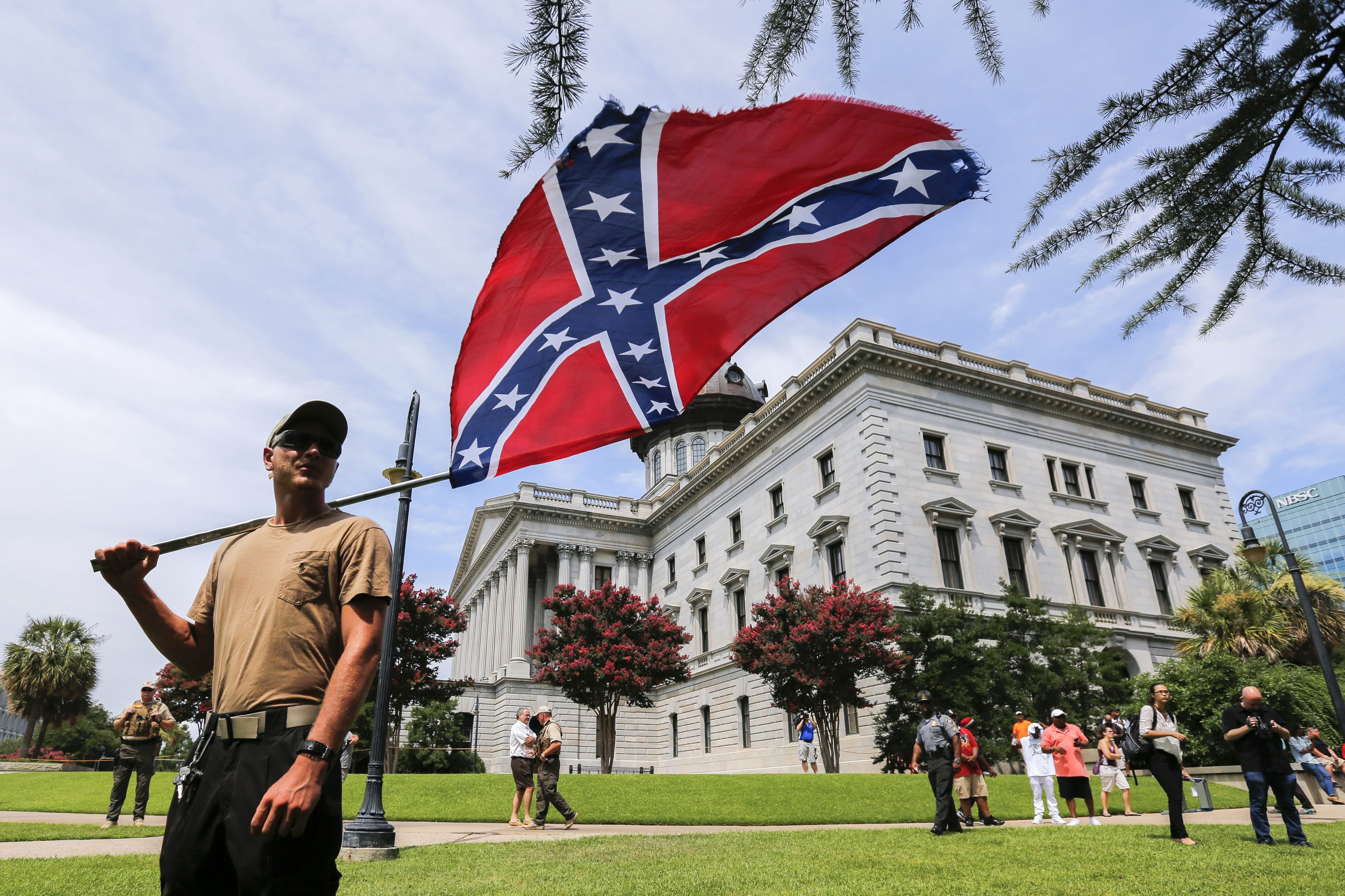 A man displays a Confederate battle flag during New Black Panther Party and Ku Klux Klan rallies on the grounds of the South Carolina Capitol in Columbia, S.C. on July 18, 2015.