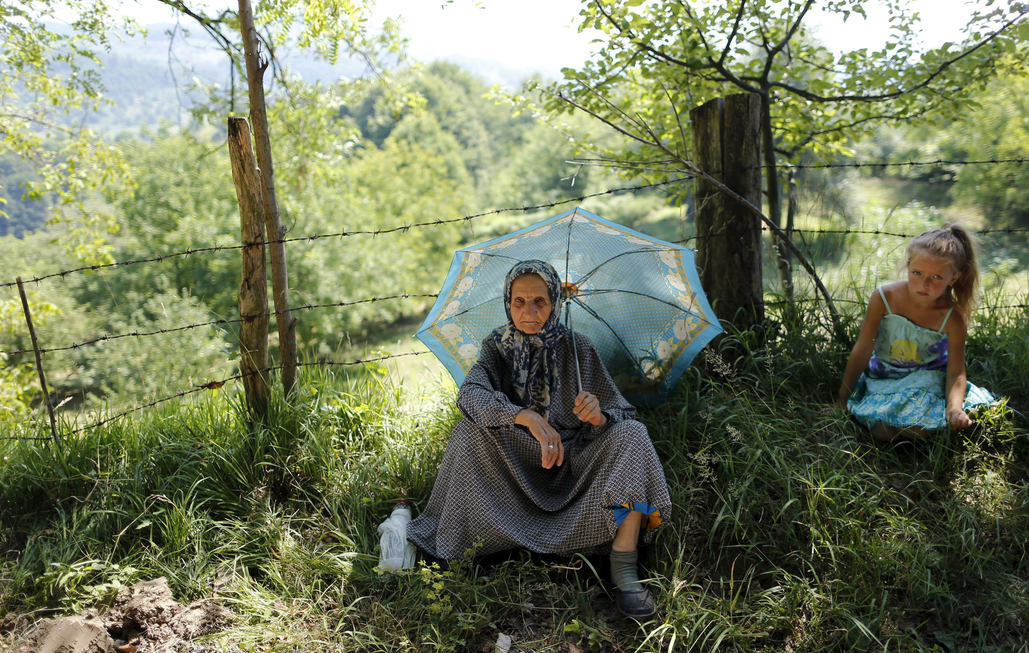 An elderly woman sitting under an umbrella watches as people take part in a march near the village of Nezuk, in Bosnia on July 8, 2015.
