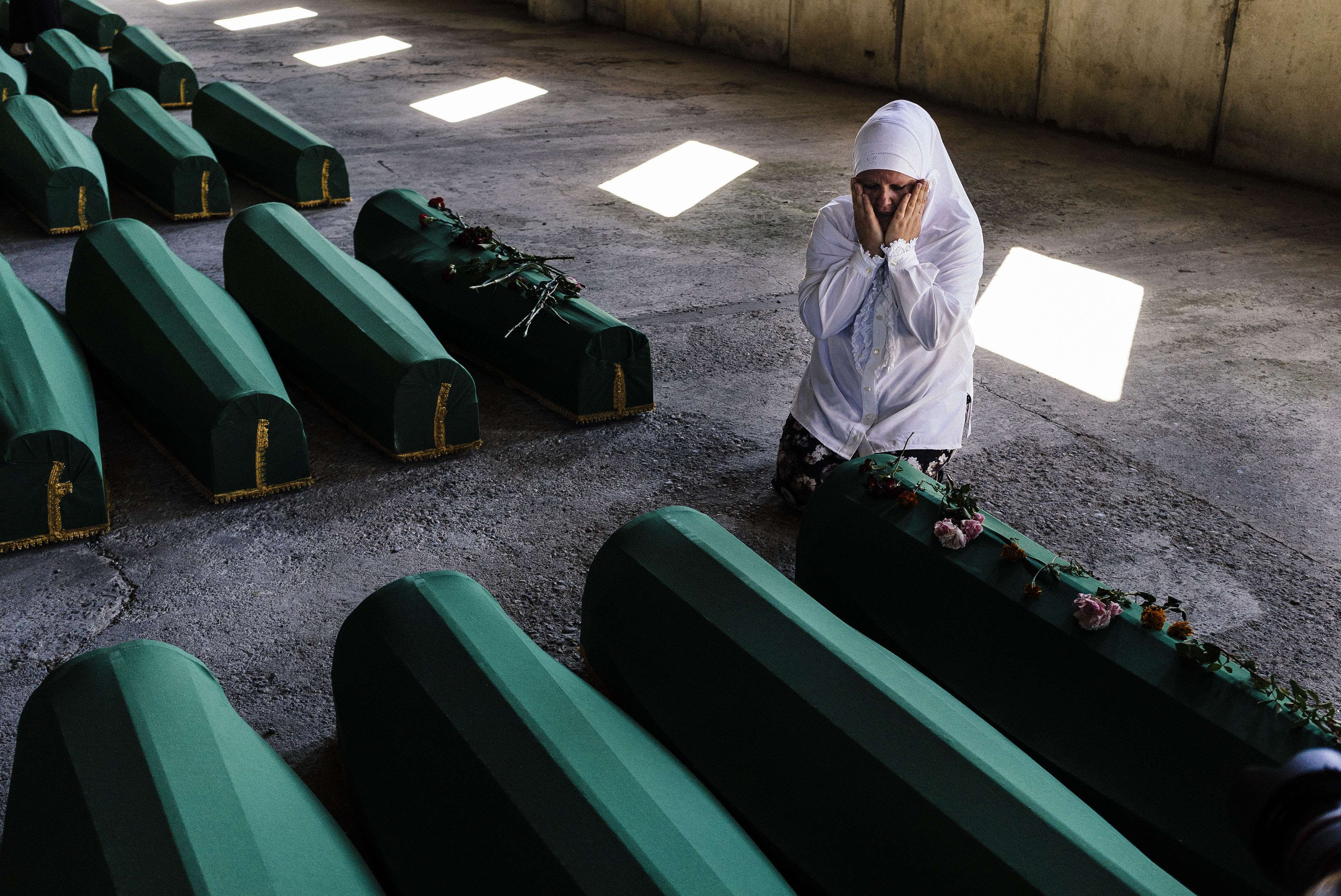 A Bosnian woman mourns next to the coffin of a relative among 136 newly identified victims of the 1995 Srebrenica massacre at the Potocari Memorial Center near the eastern Bosnian town of Srebrenica on July 10, 2015.