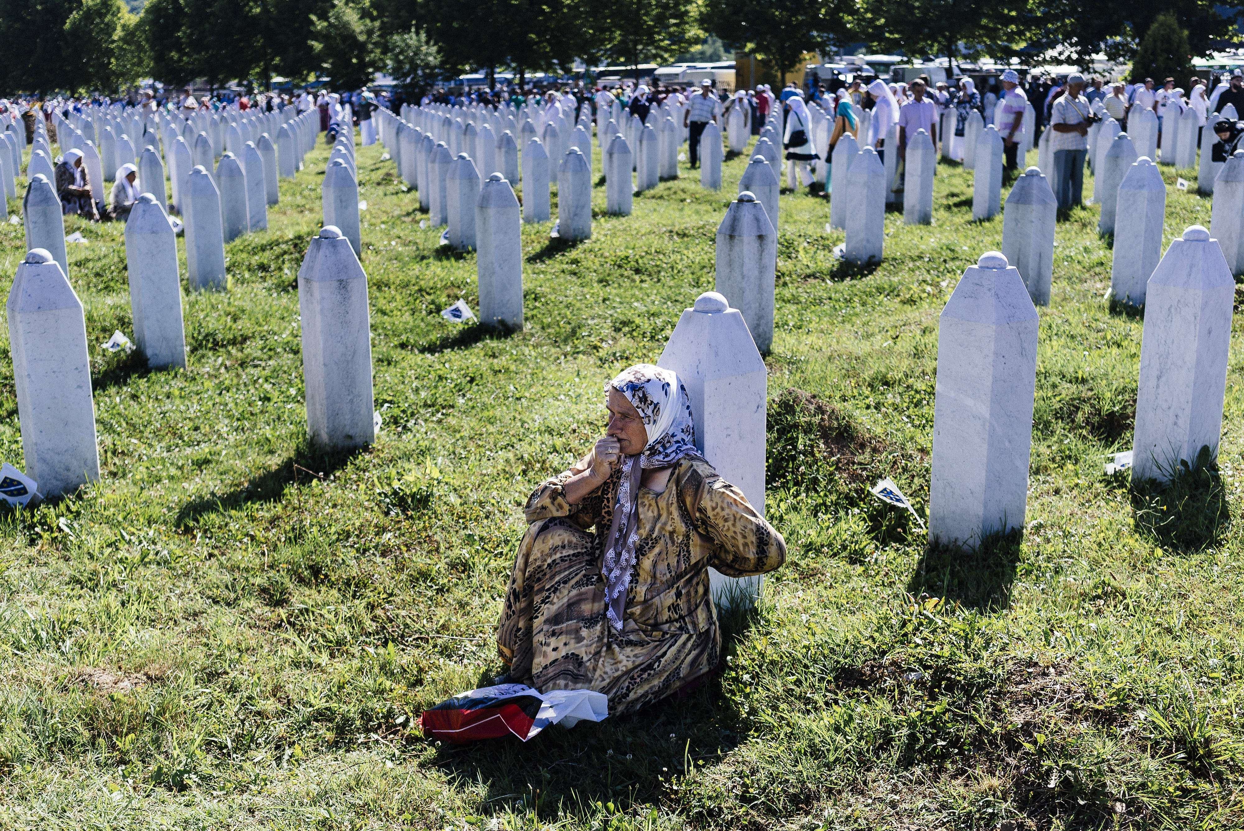 A Bosnian woman mourns at the grave of a relative on July 11, 2015 at the Potocari Memorial Center near the eastern Bosnian town of Srebrenica.