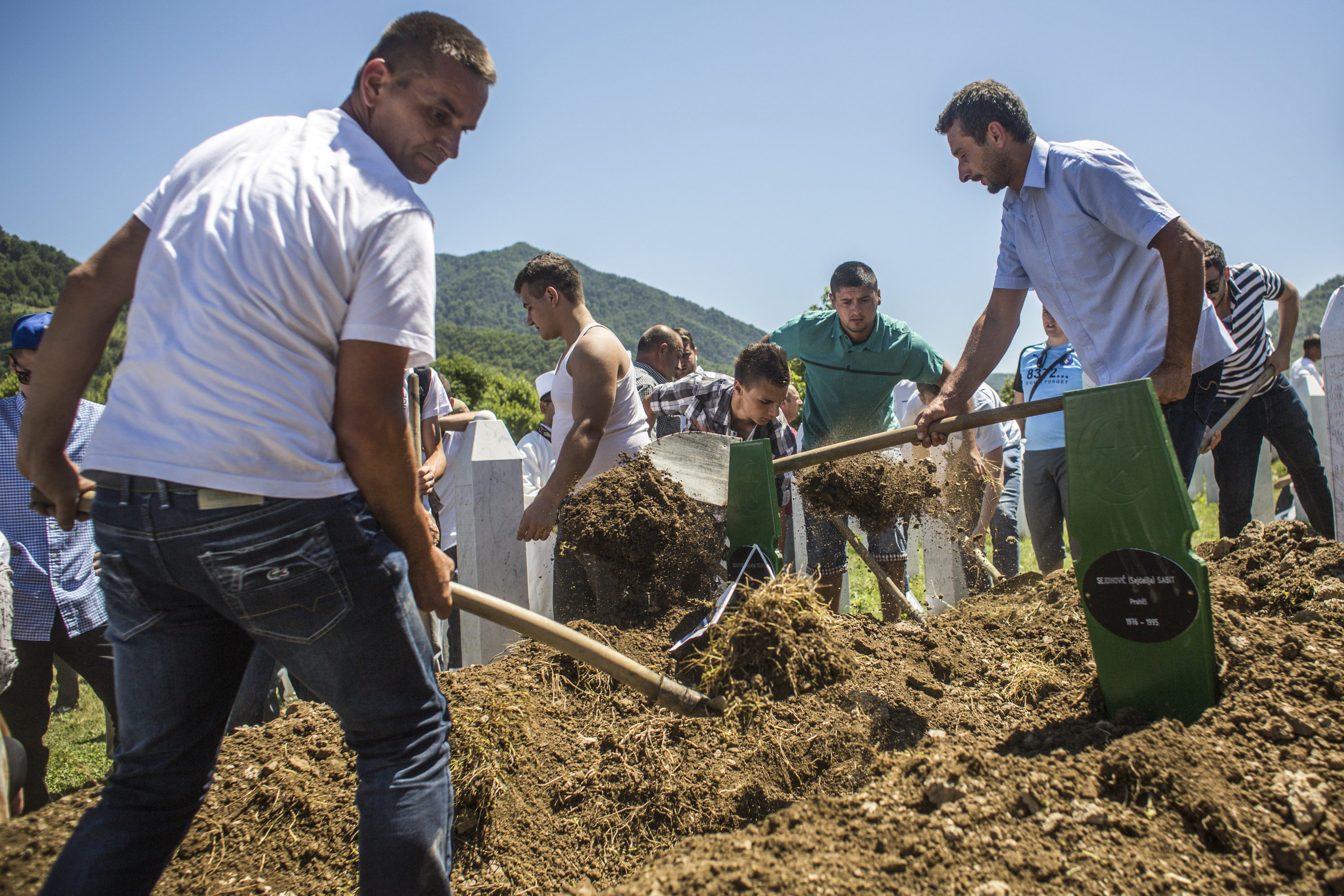 Family members and volunteers bury one of the 136 coffins of newly-identified victims of the 1995 Srebrenica massacre at the Potocari cemetery and memorial on July 11, 2015 in Srebrenica, Bosnia.