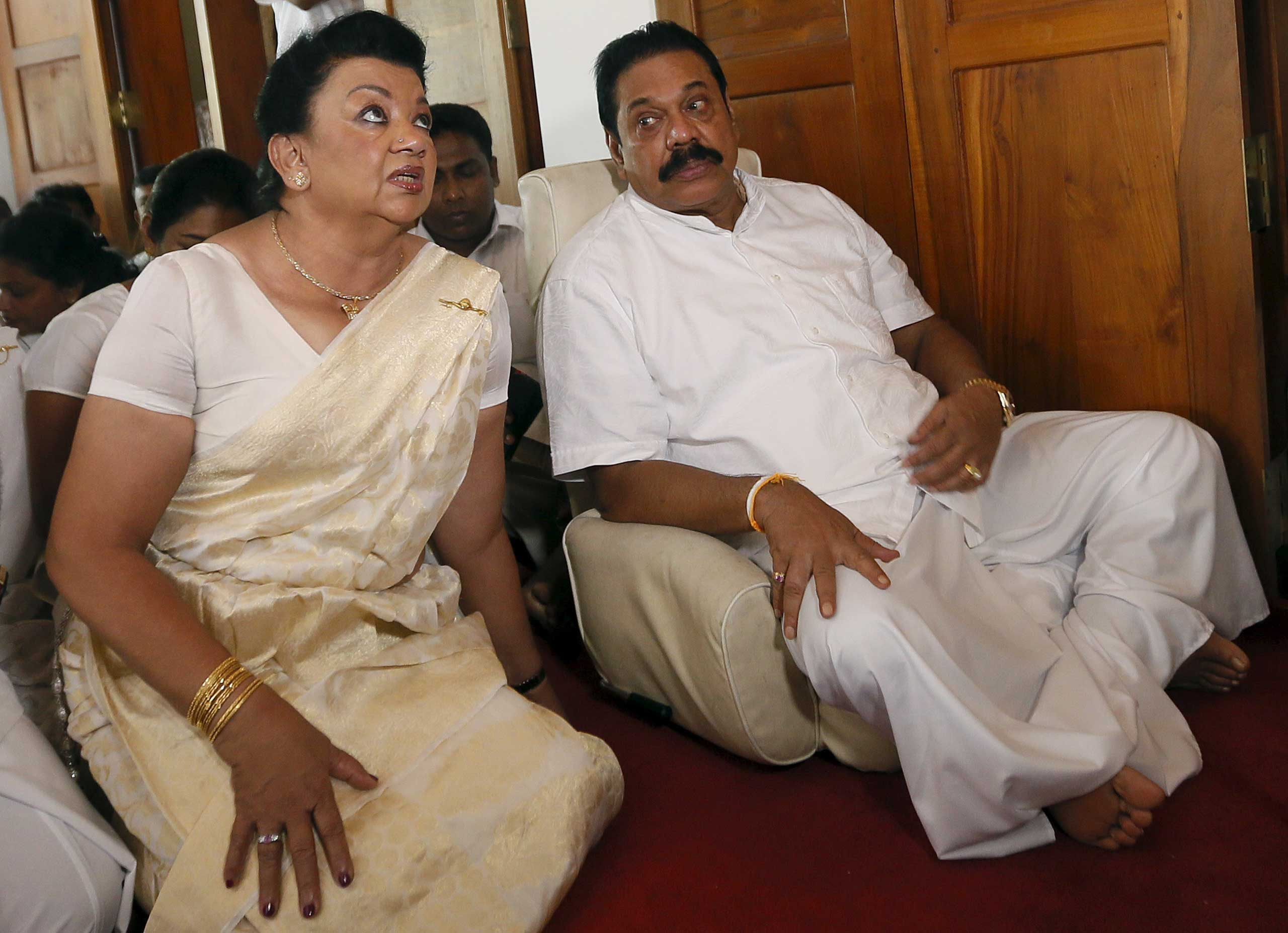 Former Sri Lankan president Mahinda Rajapaksa sits next to his wife Shiranthi Rajapaksa during a religious ceremony at his residence in Medamulana, Sri Lanka, on July 1, 2015.