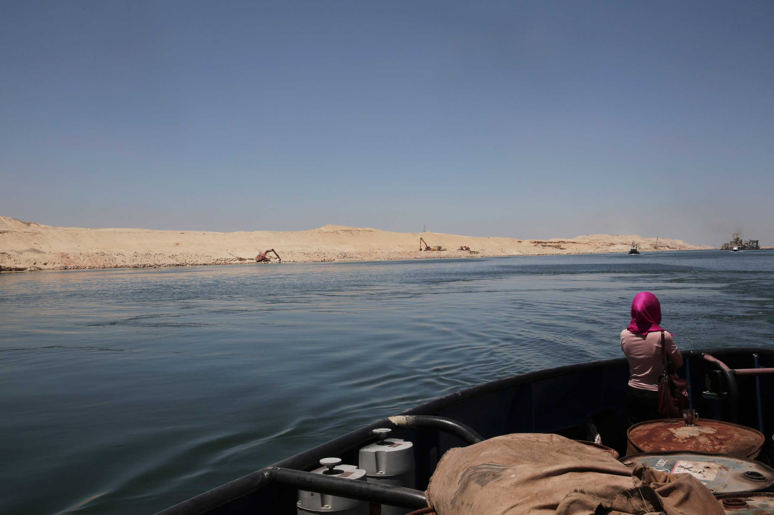 A woman looks at a new section of the Suez Canal during a media tour in Ismailia, Egypt, on July 29, 2015.