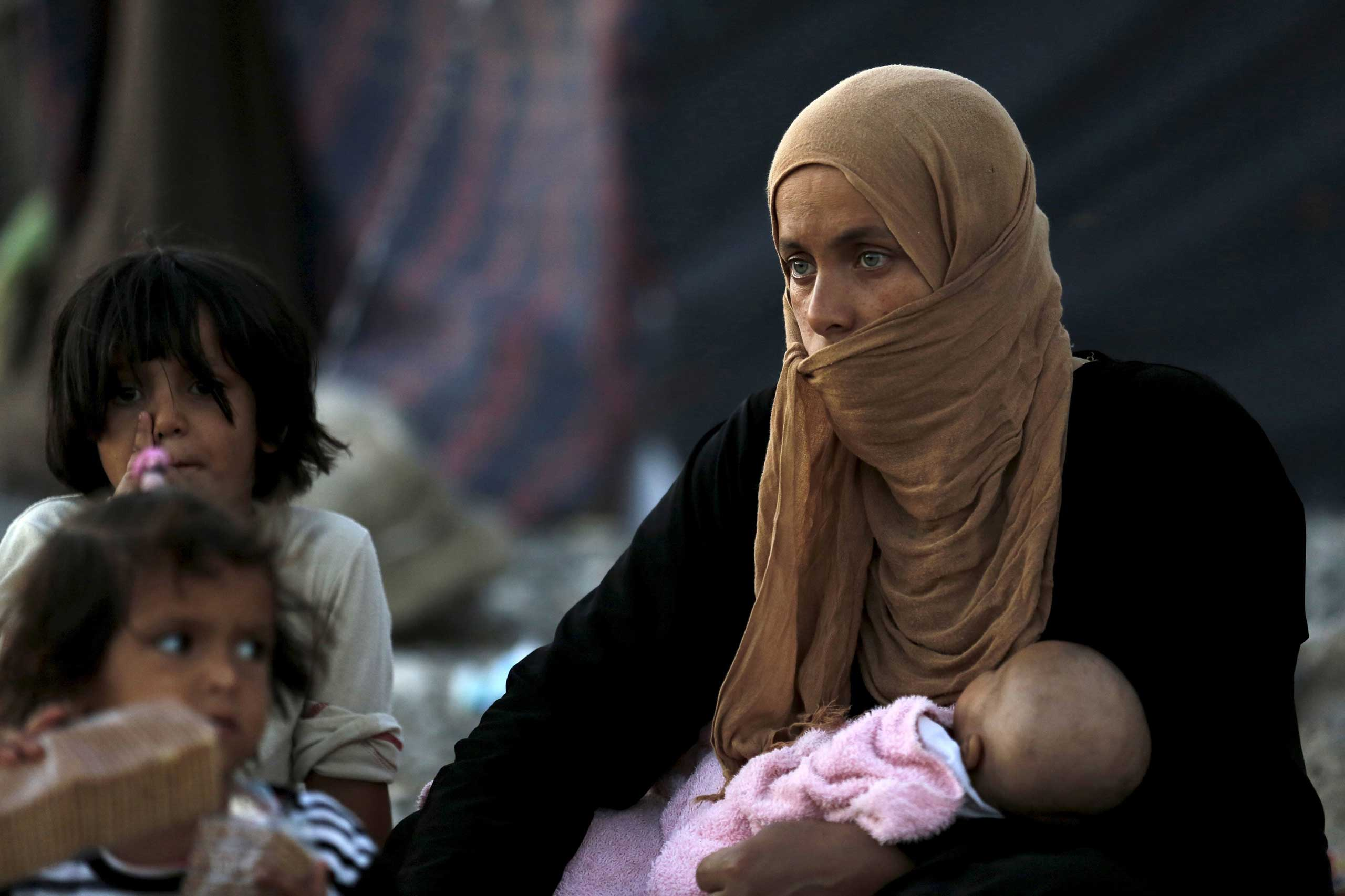 A refugee from the northern Syrian town of Tel Abyad and her children in Akcakale, in Sanliurfa province, Turkey, on June 18, 2015.