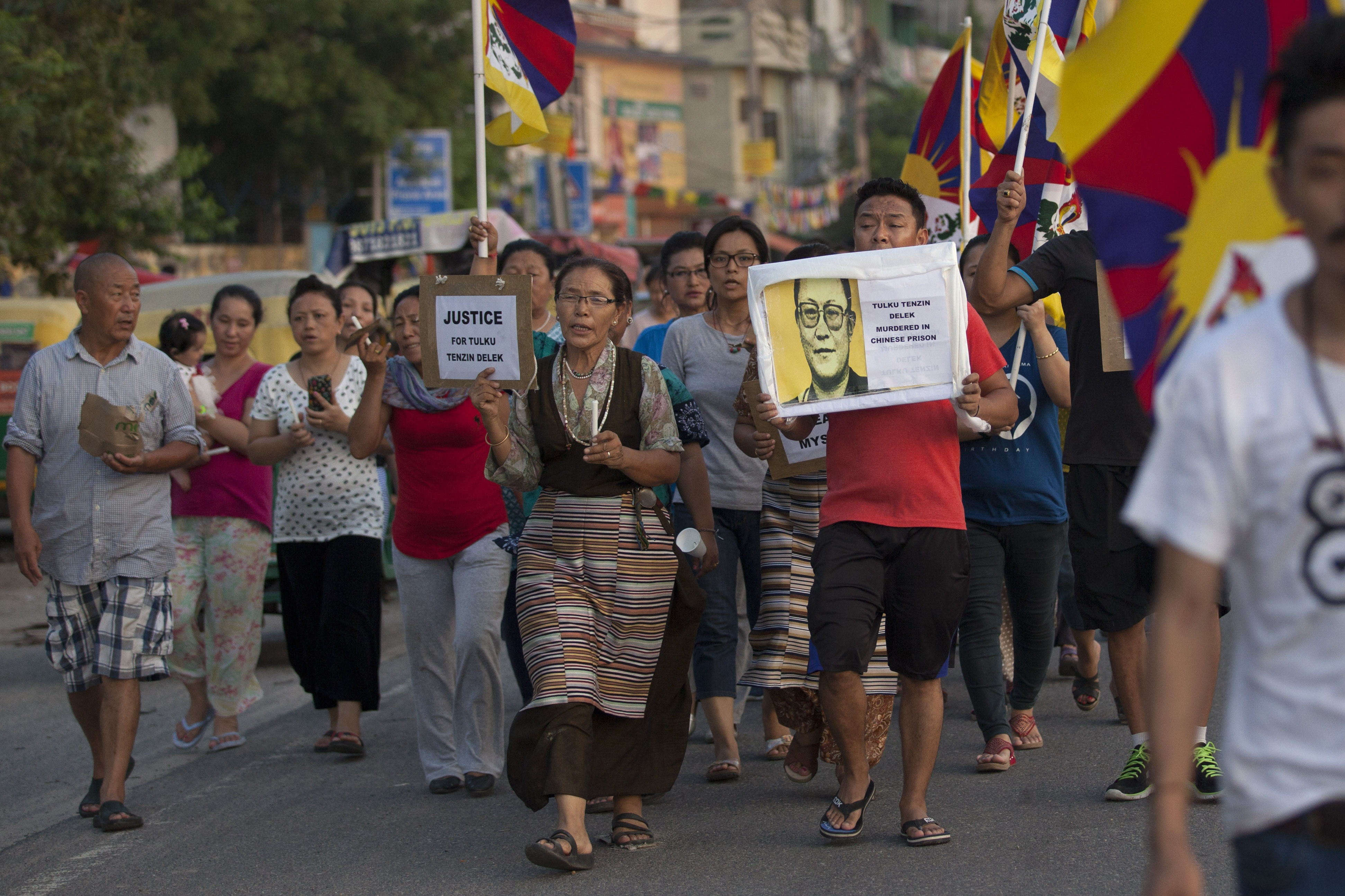 Exile Tibetans walk during a candle light vigil to remember Tibetan lama Tenzin Delek Rinpoche, in New Delhi, India, Monday, July 13, 2015.