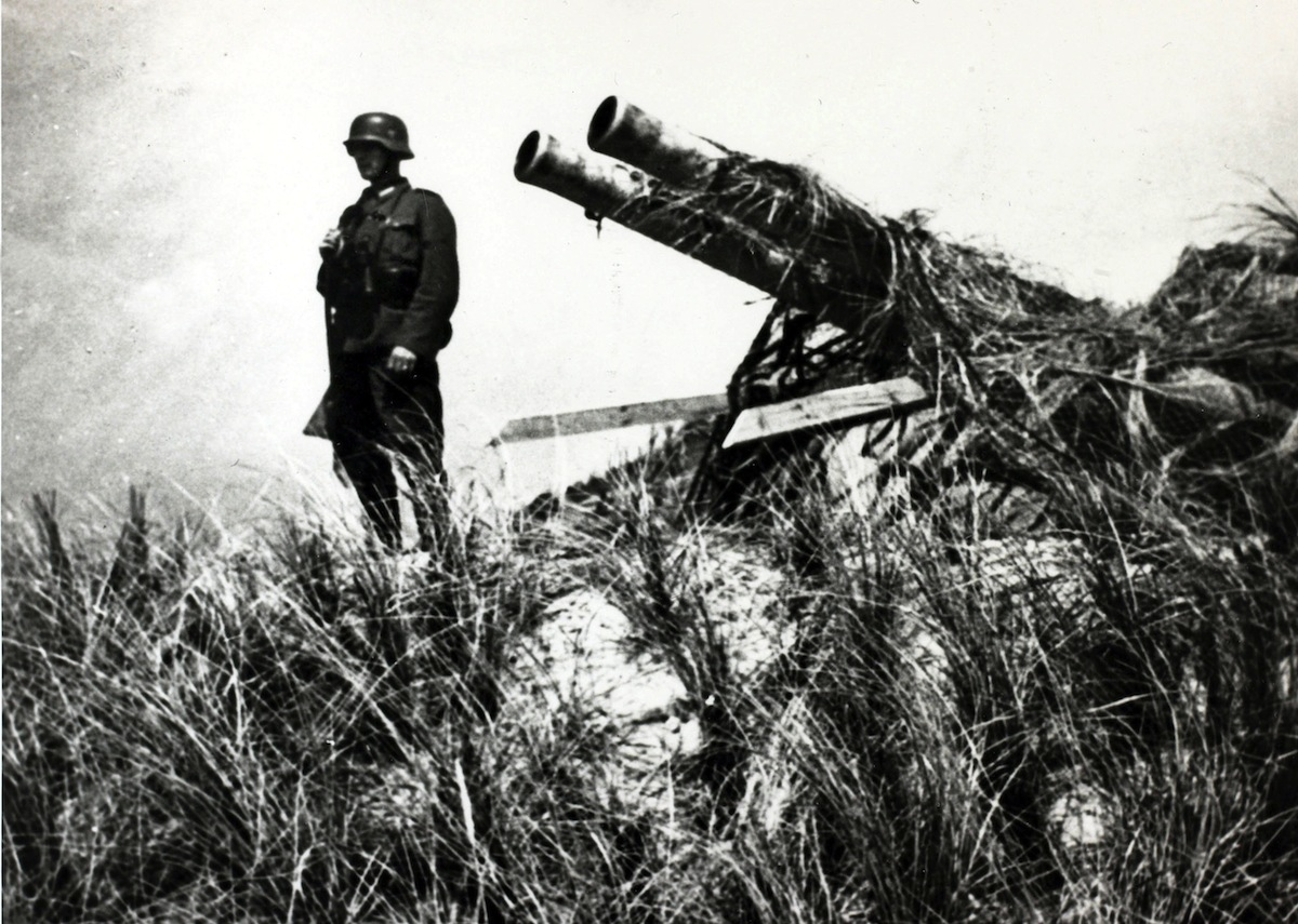 May 1940, A German soldier stands guard over a captured Dutch gun on the island of Texel