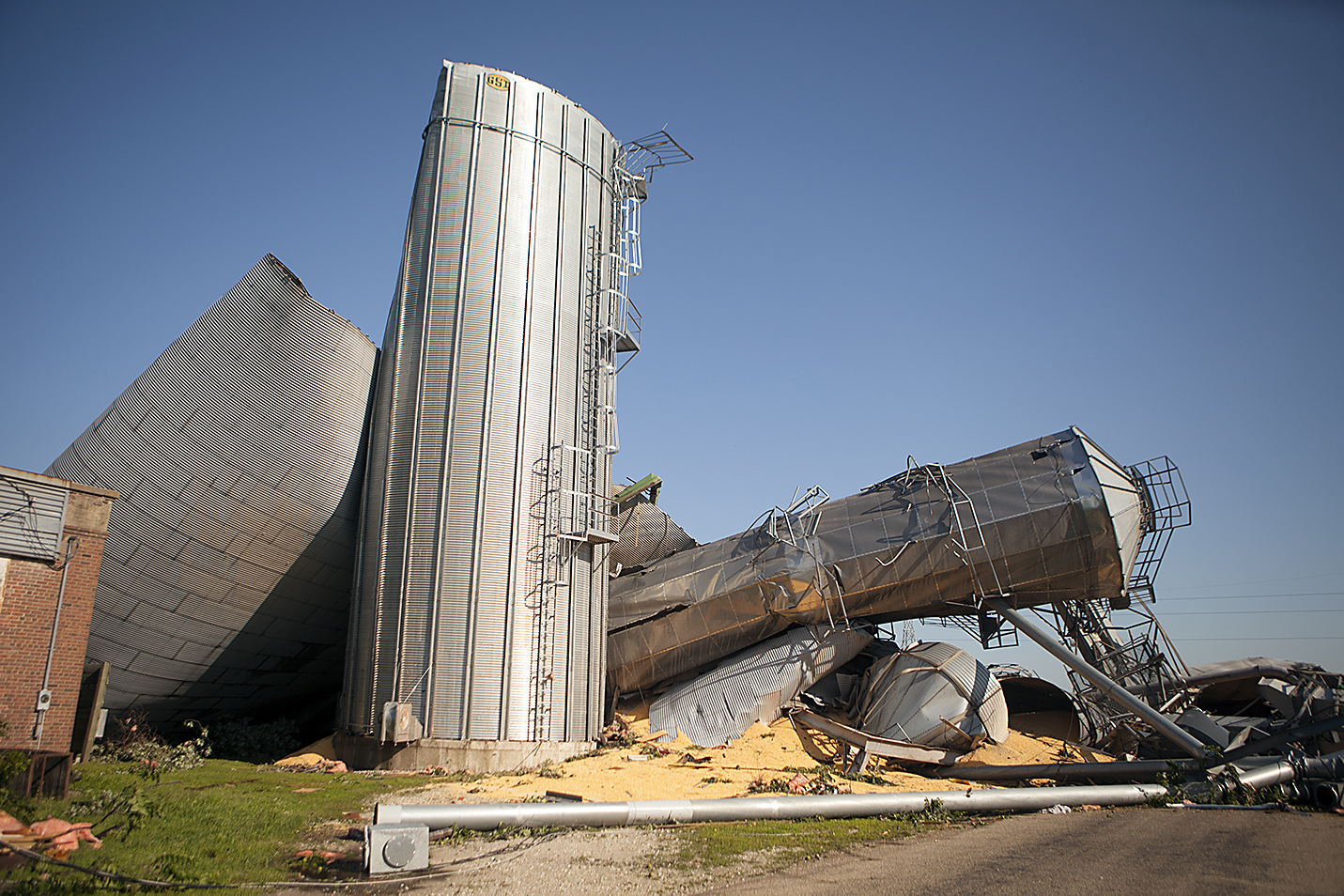 Multiple grain bins lie toppled over each other on July 17, 2015 in Cameron, Ill., the morning after a tornado swept through the city.