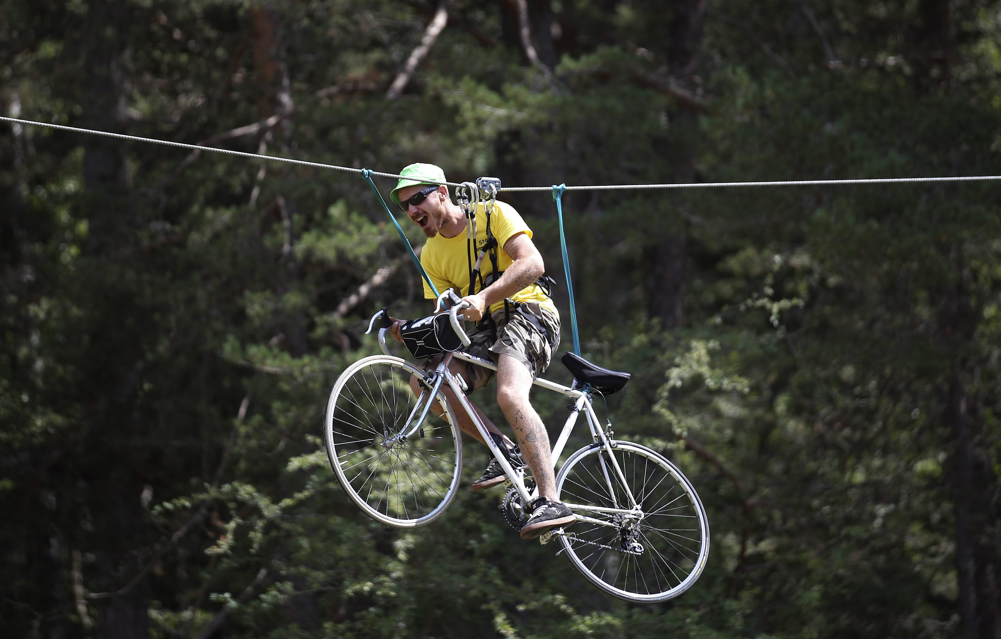 A fan rides a bicycle as he is suspended from a cable during the 17th stage of the race from Digne-les-Bains to Pra Loup in the French Alps mountains on July 22, 2015.