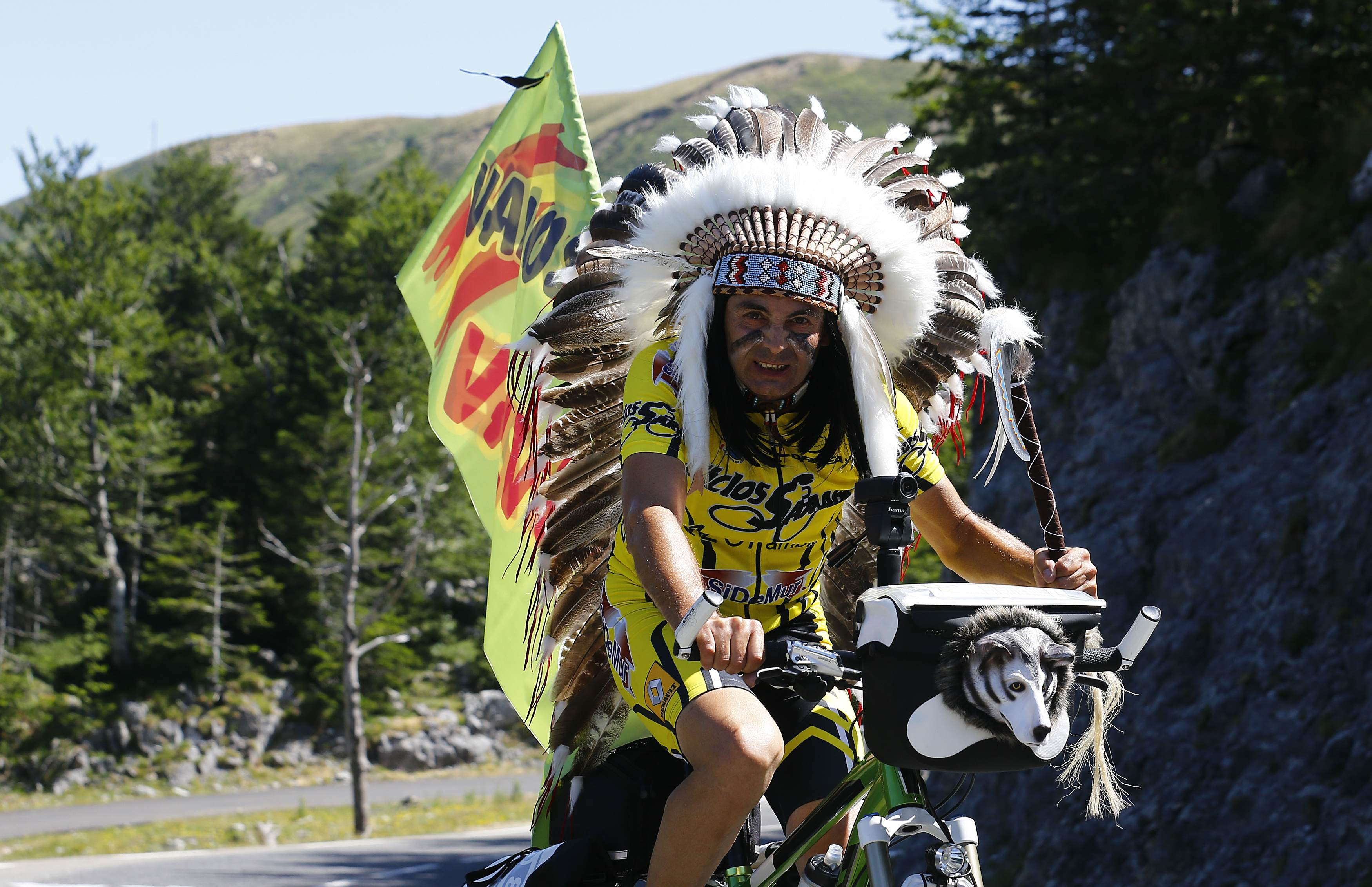 A supporter of Movistar rider Alejandro Valverde of Spain, dressed as an American Indian, rides his bicycle before the 10th stage of the race from Tarbes to La Pierre-Saint -Martin, France on July 14, 2015.