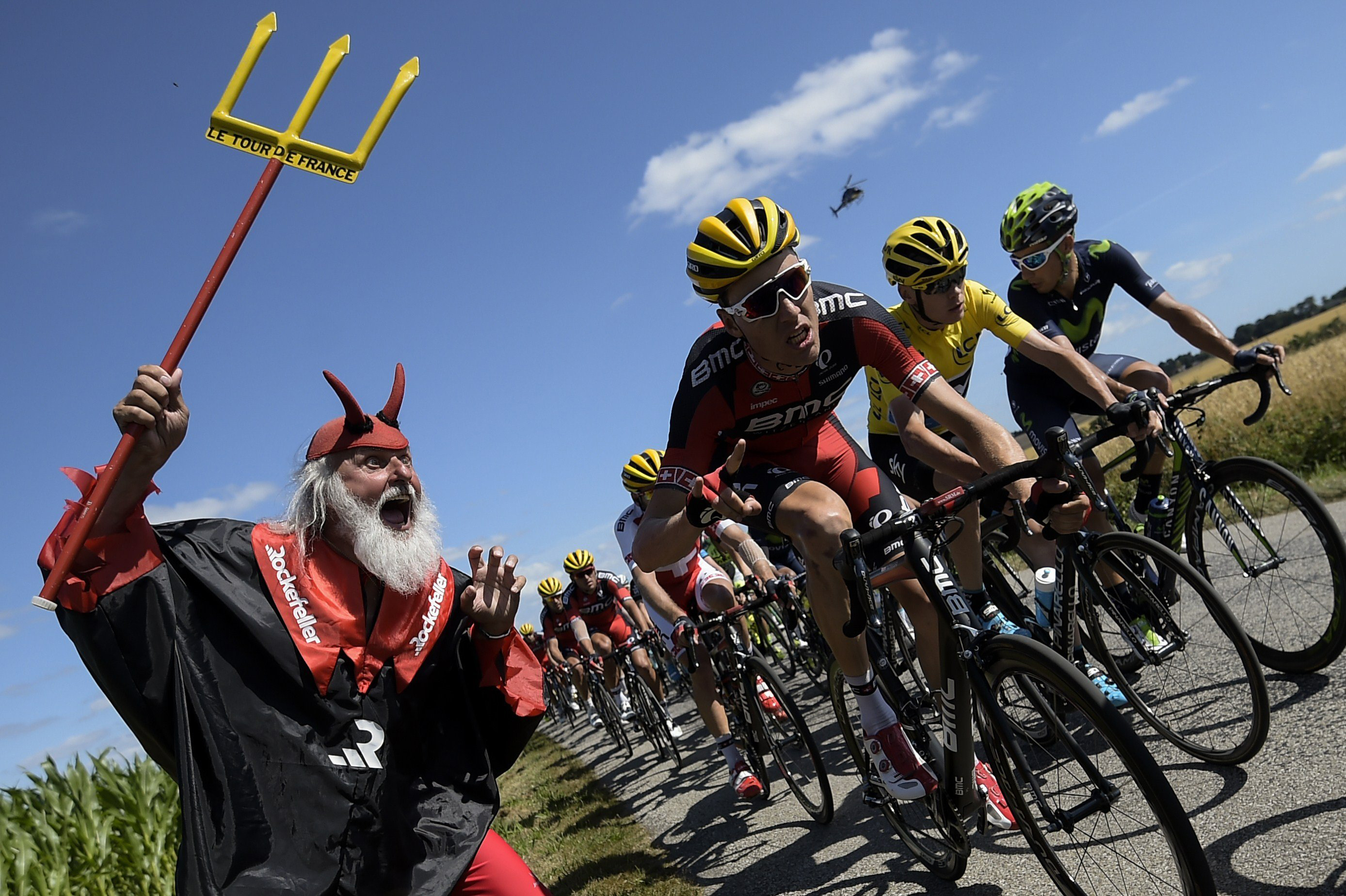 German supporter Didi Senft known as El Diablo cheers as Great Britain's Christopher Froome (in yellow) rides in the pack during the eighth stage of the race on July 11, 2015, between Rennes and Mur-de-Bretagne, western France.