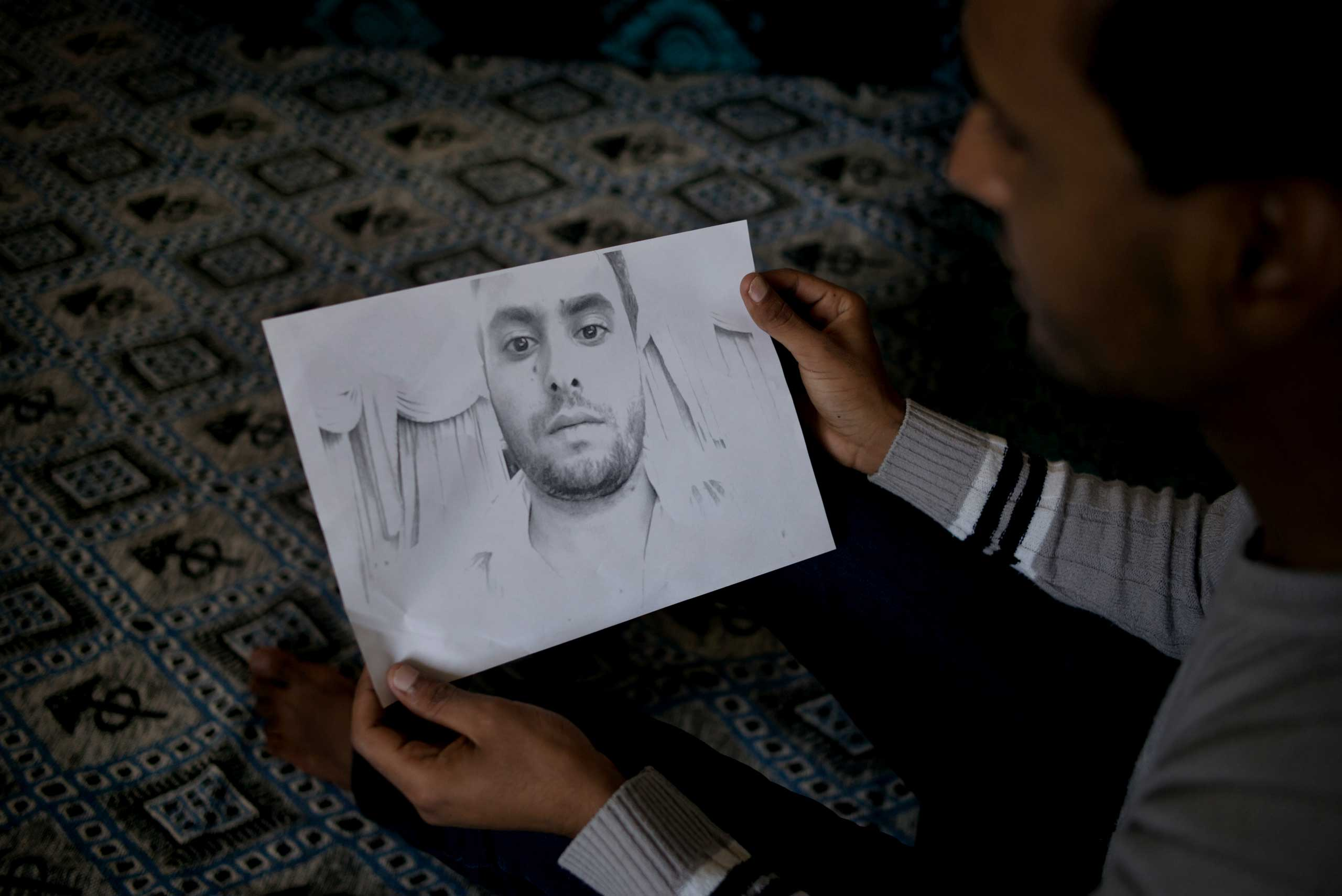 Amine Sayehi holds a sketch of his brother Anis, a university professor who suddenly left their central Tunisian town of Sidi Bouzid on Feb. 22 2014. He called home two days later from Turkey but the family believe he was killed in the Syrian city of Aleppo less than a month later. They still don't know the exact details of how or when he died.