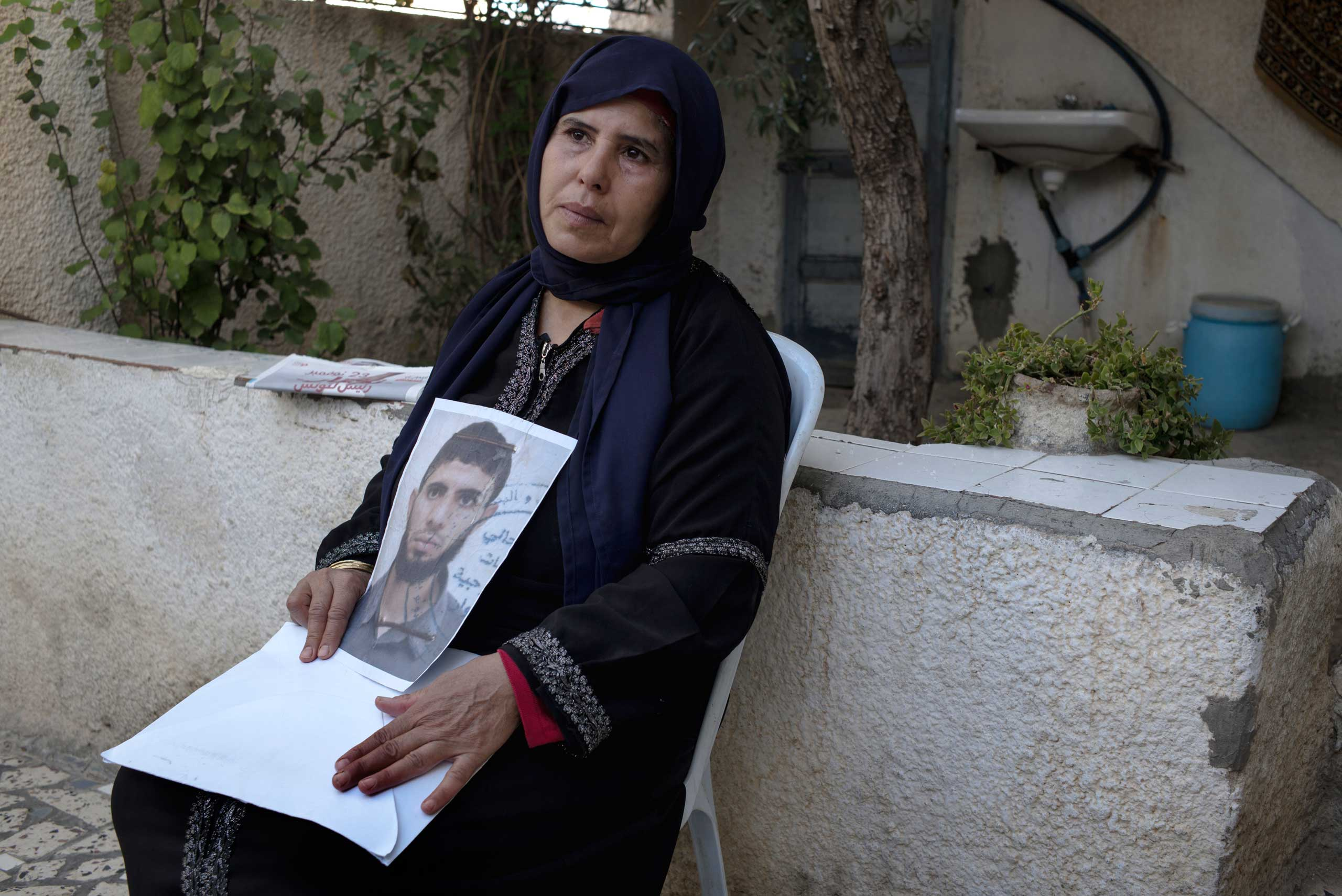 Idoudi Kaabi holds a photo of her son, Bilel, who left their small hilltop town of Oueslatia with four friends on Sept. 16. Bilel, a 23-year-old business management graduate, told his mother he was going to the funeral of a friend's father in a nearby town, but actually headed south to train in a jihadist camp in neighboring Libya. On Oct. 18, the Kaabi family received news that Bilel had killed himself and at least 20 others in a suicide attack in the Libyan city of Benghazi.