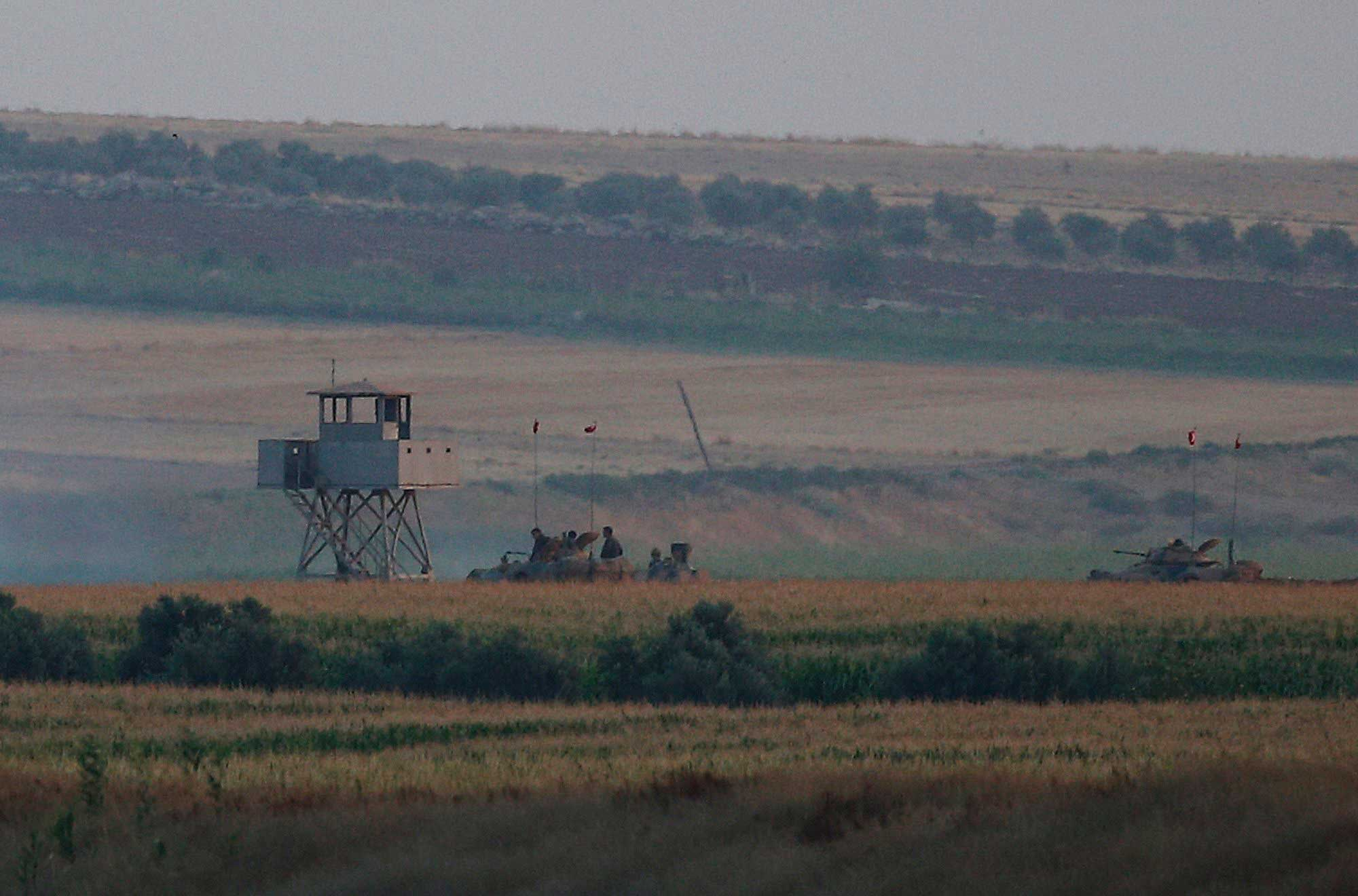 Turkish army tanks hold positions next to an outpost, near the border with Syria, on July 23, 2015.