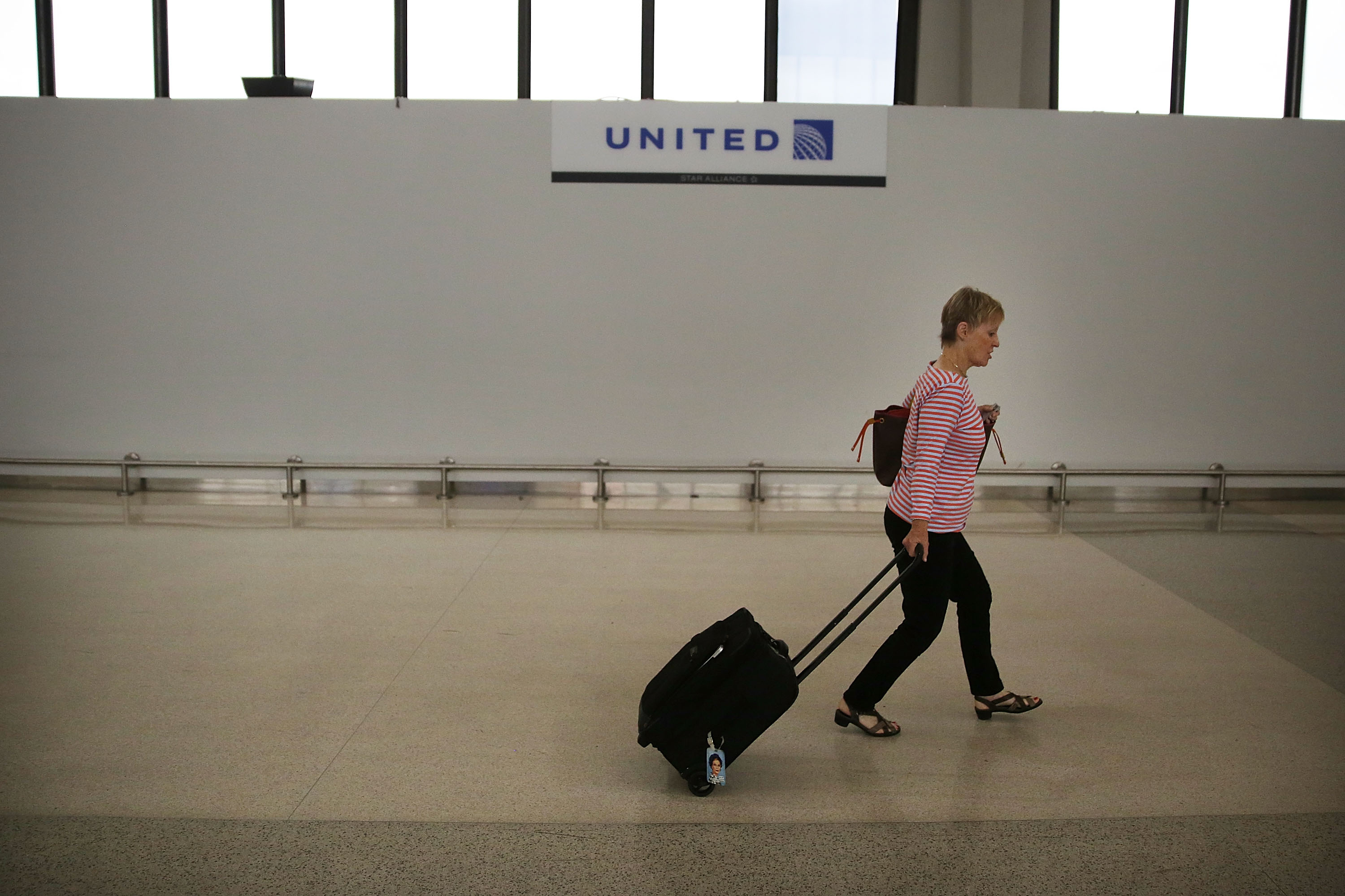 A traveler walks through the United Airlines terminal at Newark Liberty Airport on July 8, 2015 in Newark, New Jersey.