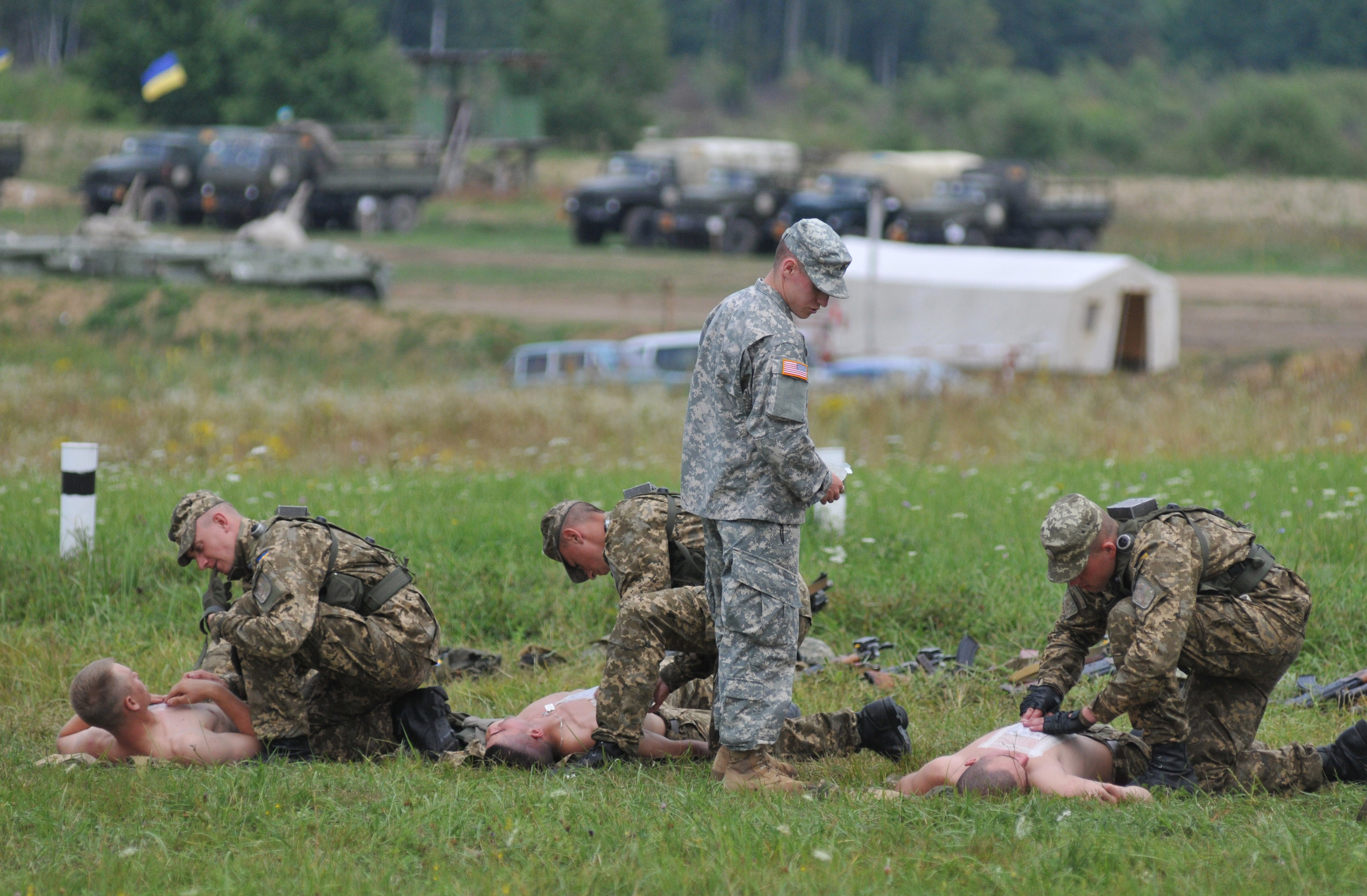 A US serviceman teaches Ukrainian soldiers how to give emergency medical aid during the Rapid Trident/Saber Guardian 2015 military exercises at the International Peacekeeping and Security Centre base outside Lviv, Ukraine on July 24, 2015.