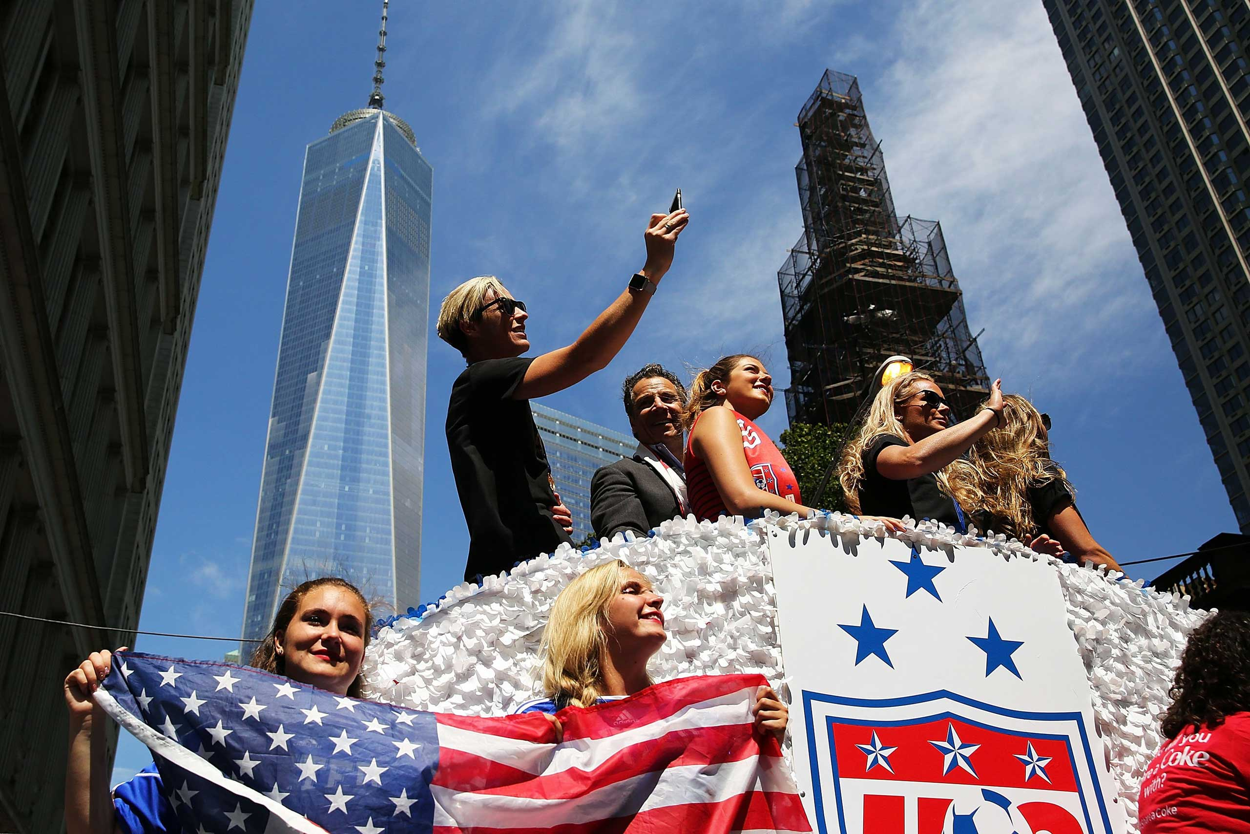 The World Cup-winning U.S. women's soccer team, including Abby Wambach (Top left), celebrates along with New York Governor Andrew Cuomo (center), as they make their way up the The Canyon of Heroes during a  ticker-tape parade along Broadway in New York City on July 10, 2015.
