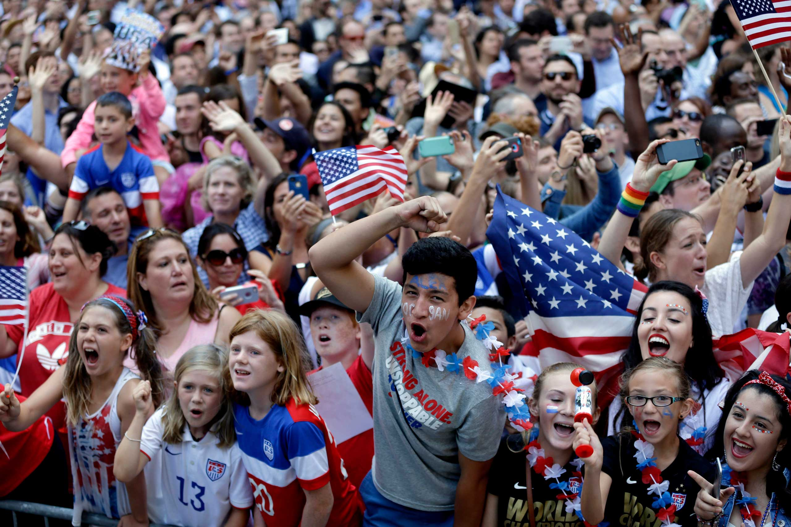 Fans of the U.S. women's soccer team cheer during the ticker tape parade to celebrate their World Cup victory, in New York City on July 10, 2015.