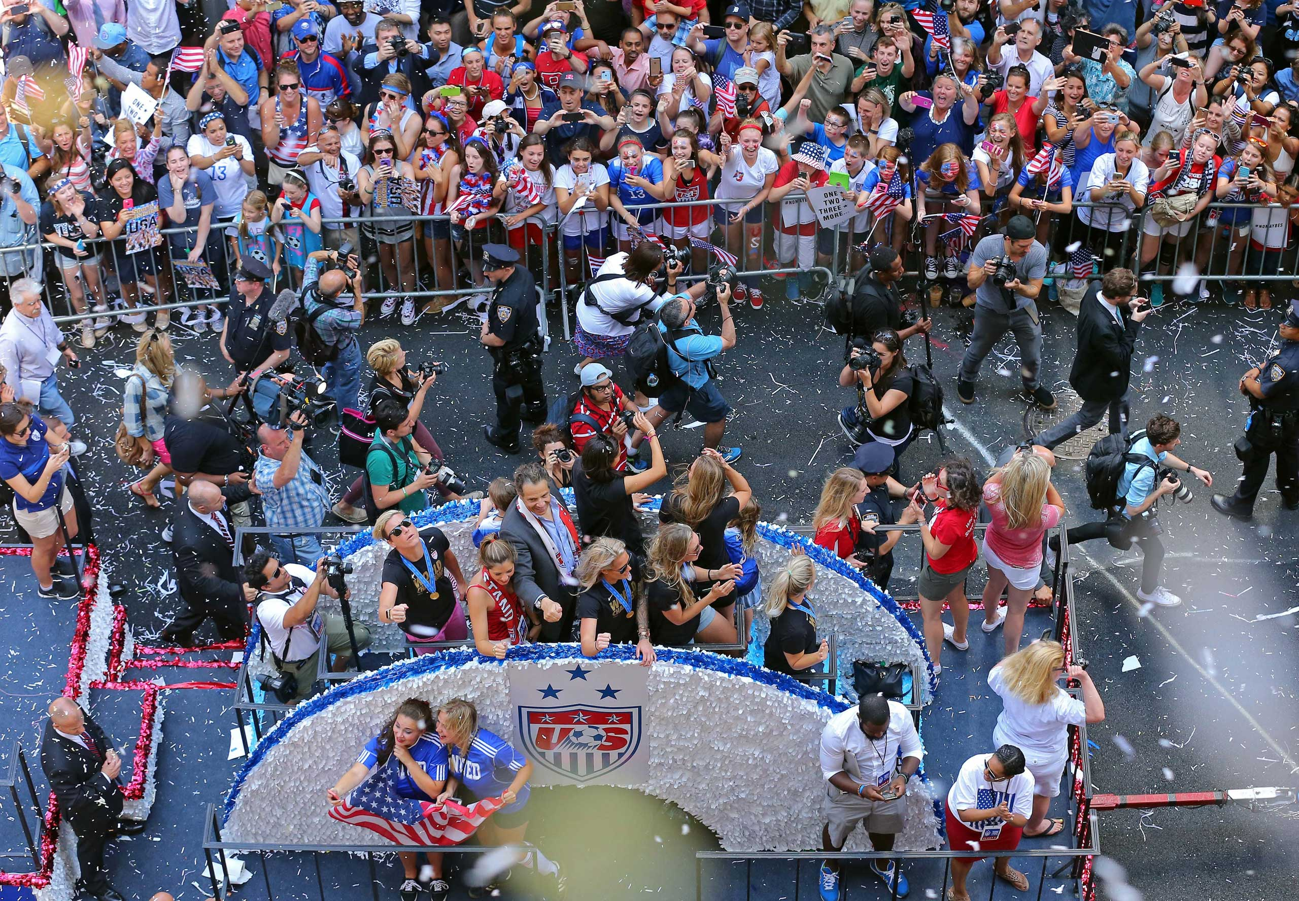 New York Governor Andrew Cuomo, at center on float, gestures during a ticker tape parade for the U.S. women's soccer team in New York City on July 10, 2015.
