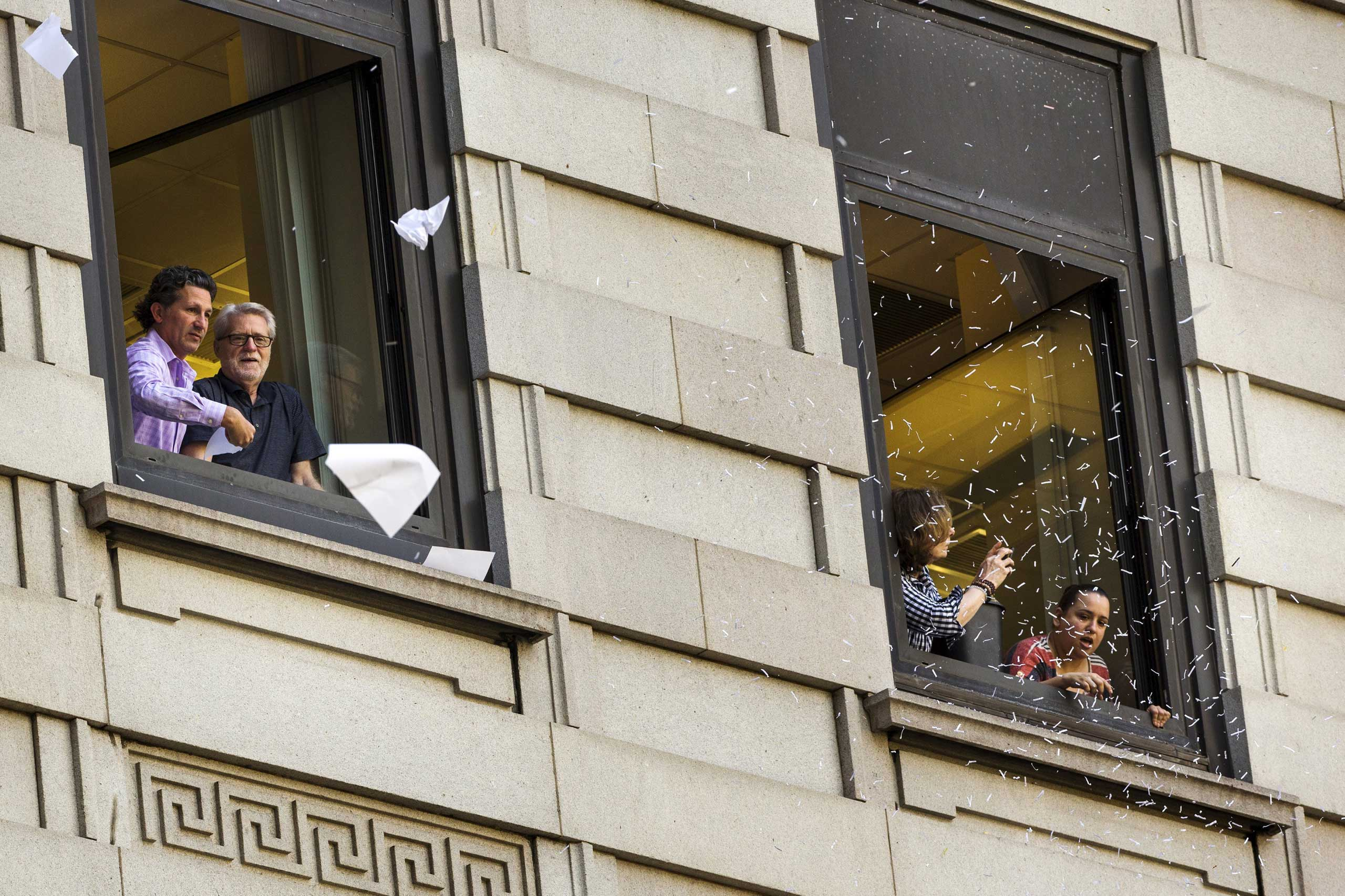 Fans of the U.S. women's soccer team throw confetti out of office windows as members of the team take part in a ticker tape parade in New York City on July 10, 2015.