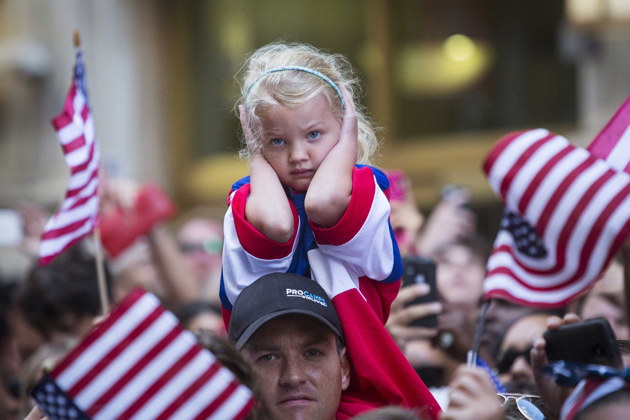 A young fan of the U.S. women's soccer team blocks her ears during the ticker tape parade to celebrate their World Cup final win over Japan on Sunday, in New York on July 10, 2015.