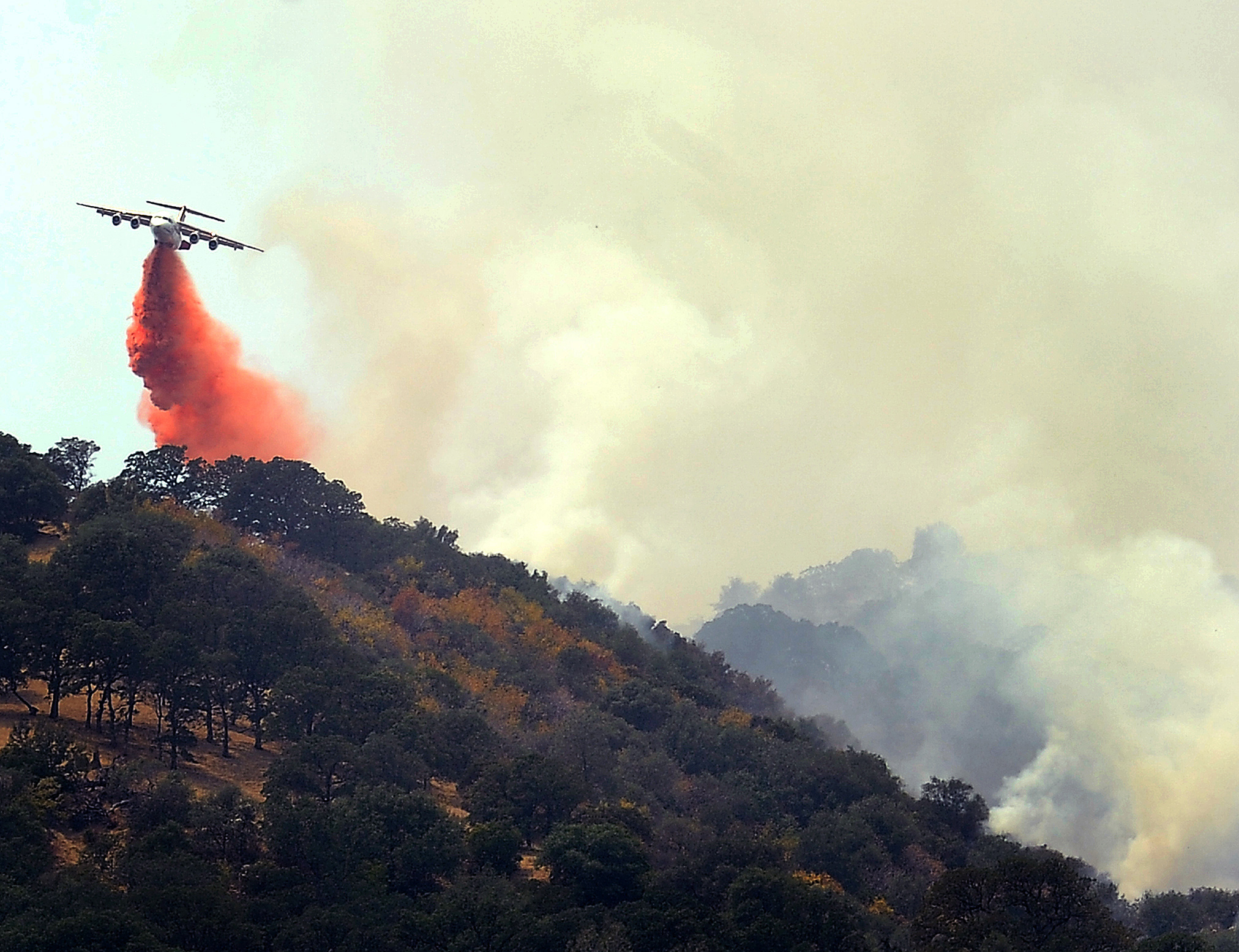 CalFire Air tanker drops fire retardant on a ridge above Pleasants Valley Rd. near Winters, Calif., as crews continue to battle the Wragg Fire on July 23, 2015.