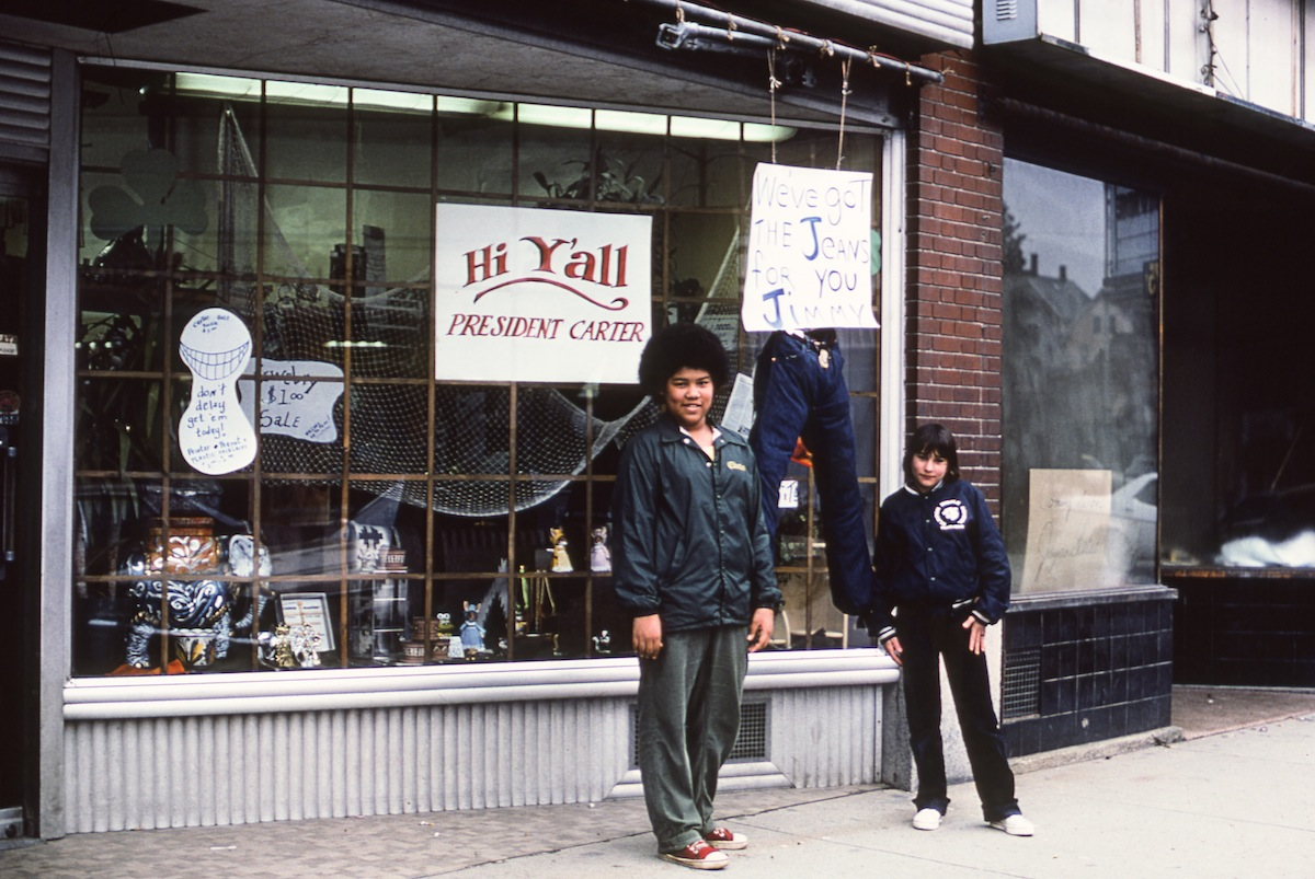 During a Presidential visit, unidentified residents stand outside a shop decorated with signs that read 'Hi Y'all President Carter' and 'We've Got the Jeans for you Jimmy,' Clinton, Mass., March 16, 1977.