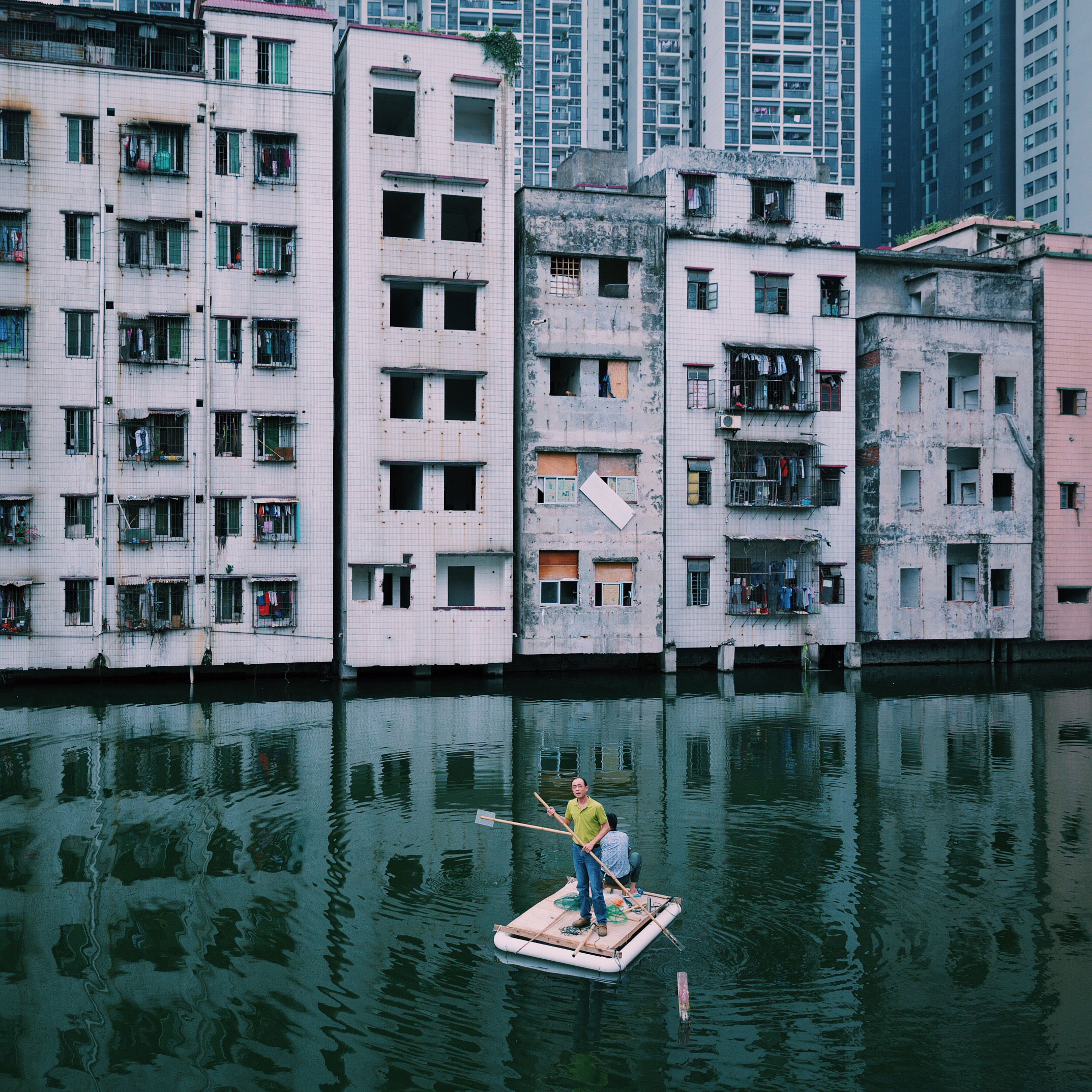 Two men fish in a pond in Xian Village, which is in the city center of Guangzhou, China. A conflict between locals and real estate developers lasts for more than seven years because of the uneven compensation and the corruption of Xian village leaders.