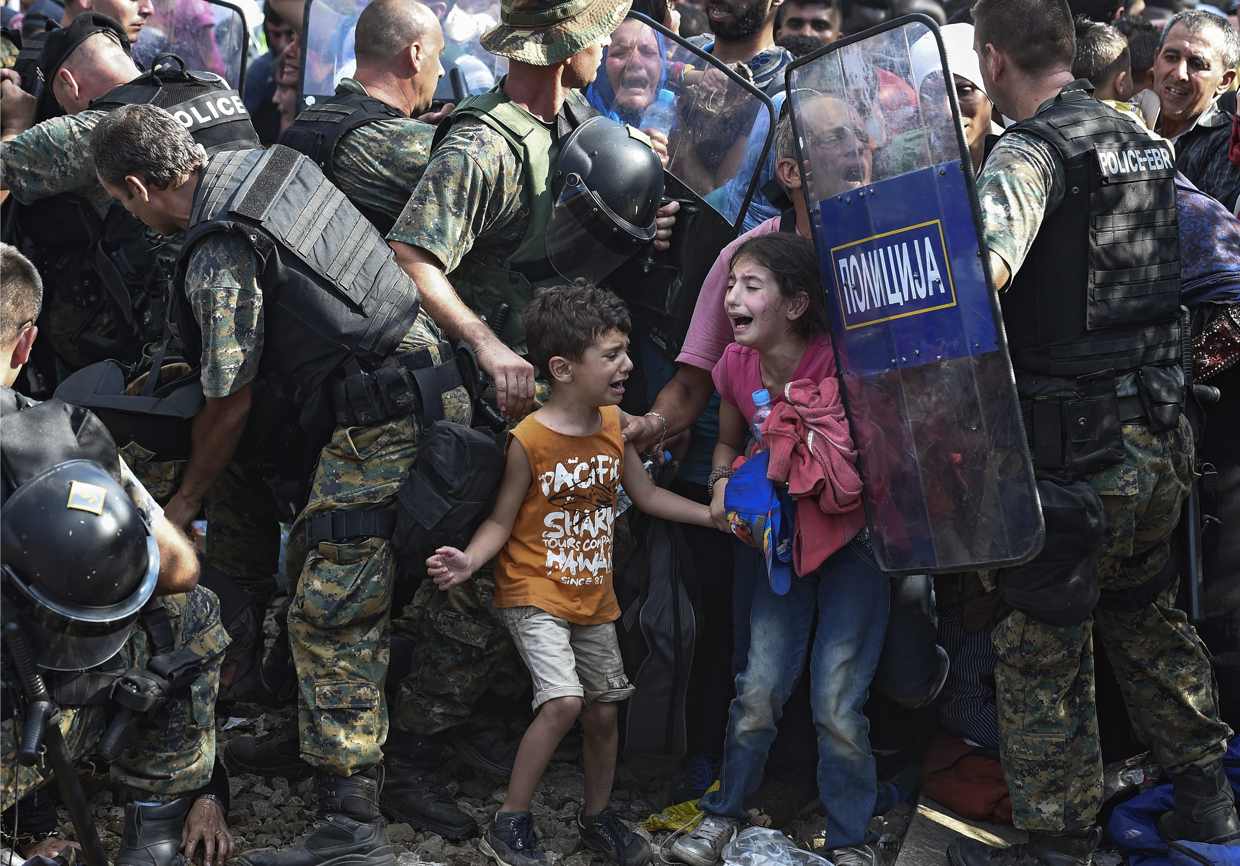 Children cry as migrants waiting on the Greek side of the border break through a cordon of Macedonian special police forces to cross into Macedonia, near the southern city of Gevgelija, The Former Yugoslav Republic of Macedonia on Aug. 21, 2015. Macedonian police clashed with thousands of migrants attempting to break into the country after being stranded in no-man's land overnight, marking an escalation of the European refugee crisis for the Balkan country.