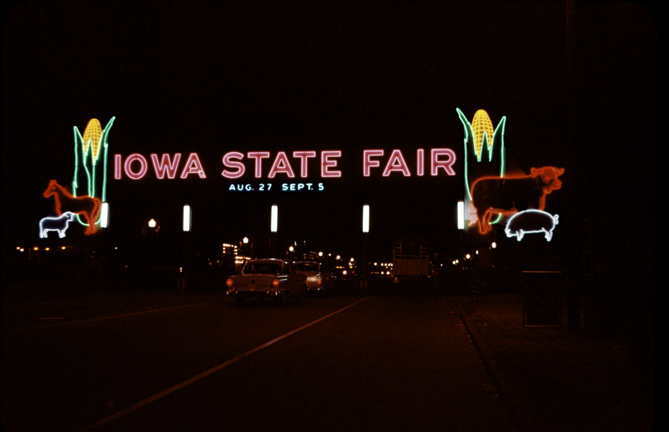 A neon sign lights up the entrance to the Iowa State Fair, 1955.