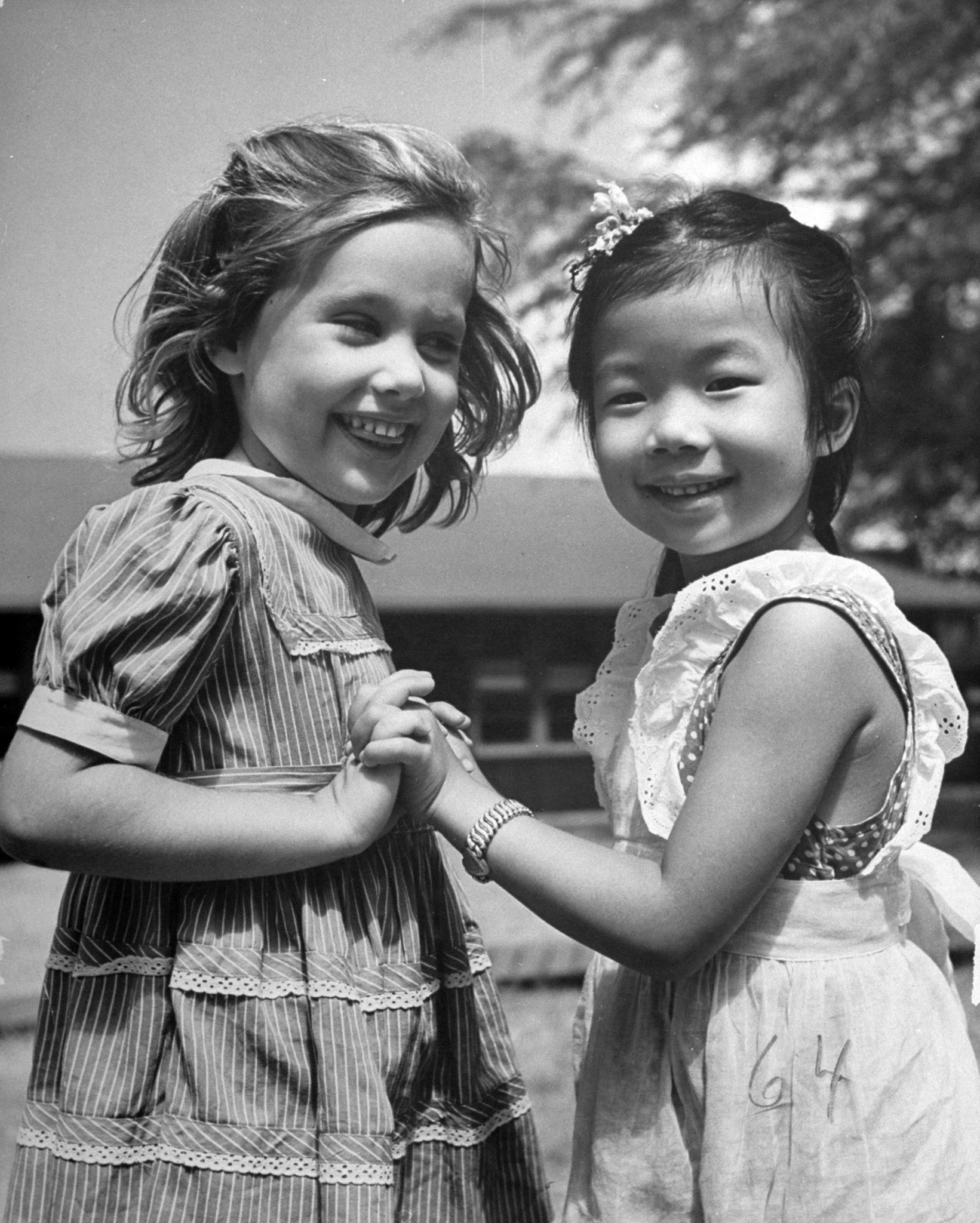 <b>Caption from LIFE.</b> Mary Lou Parker, 4, plays with Letty Mai Pang, 5, a Chinese [schoolmate], in the playground of a polyracial Honolulu school.