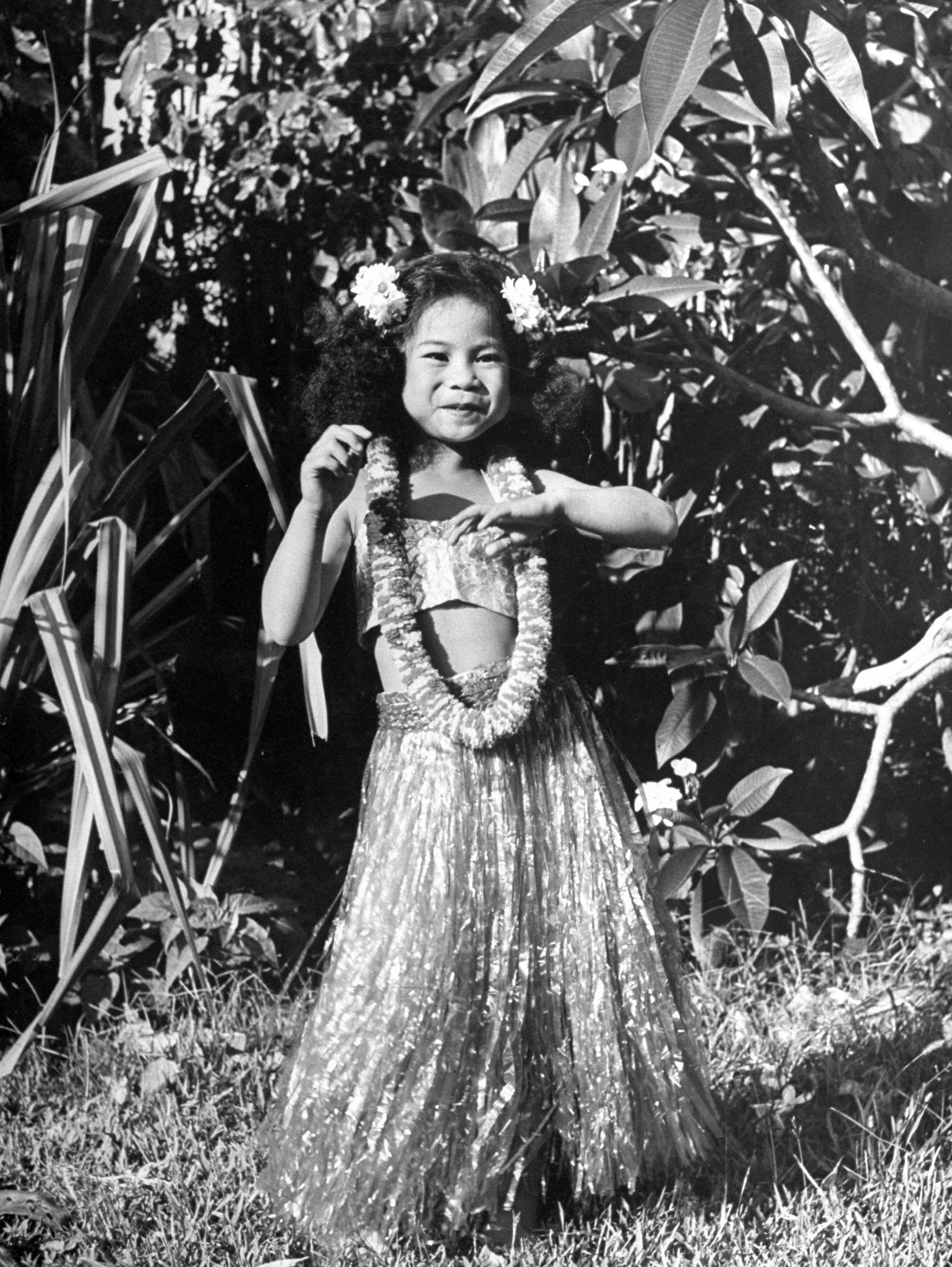 A young girl dances in a hula skirt.